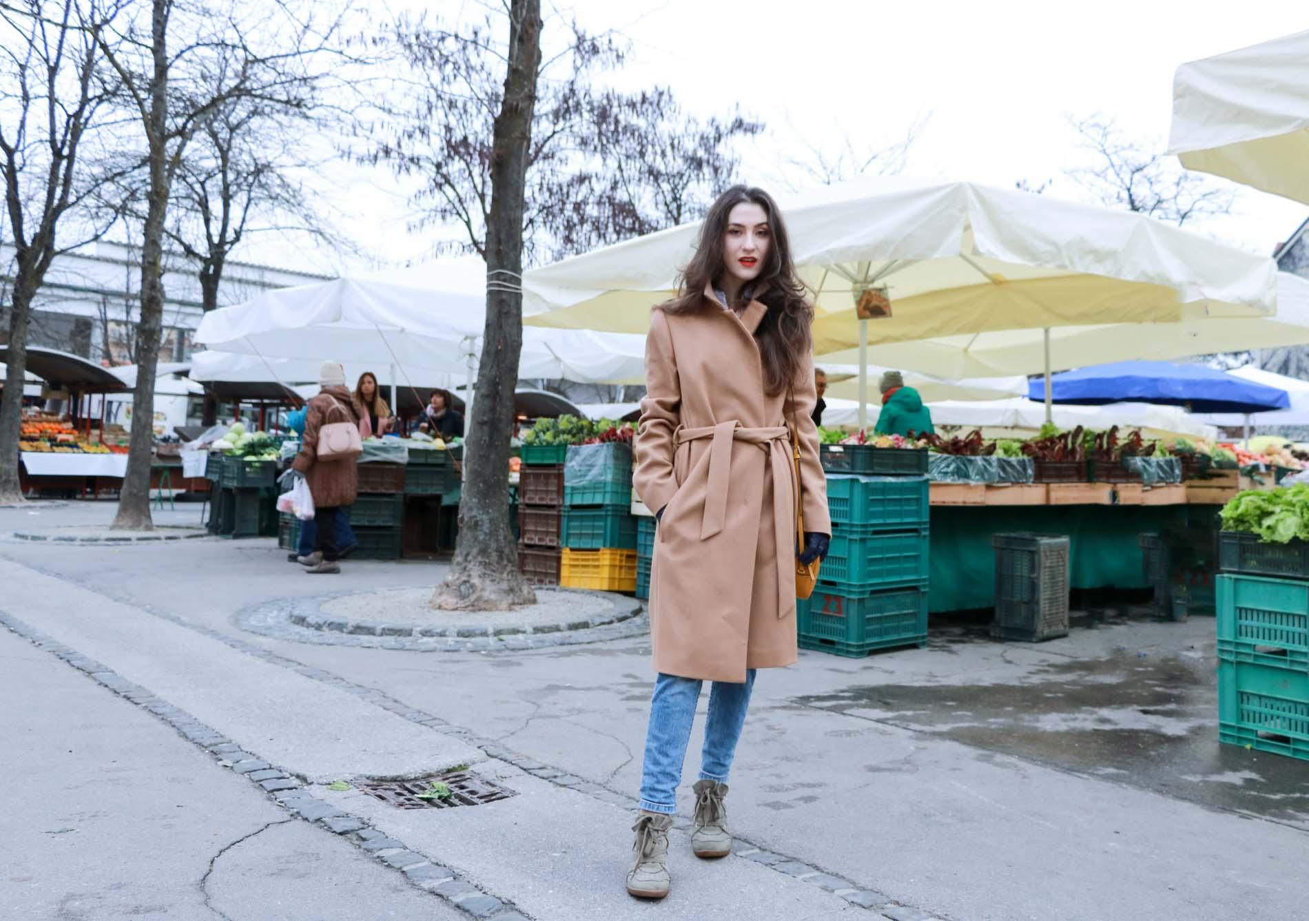 Fashion Blogger Veronika Lipar of Brunette from Wall Street wearing ESCADA wrap camel coat, A.P.C. blue jeans, Isabel Marant olive Bobby Sneakers, yellow shoulder bag from Escada, white Victorian blouse at the grocery's market