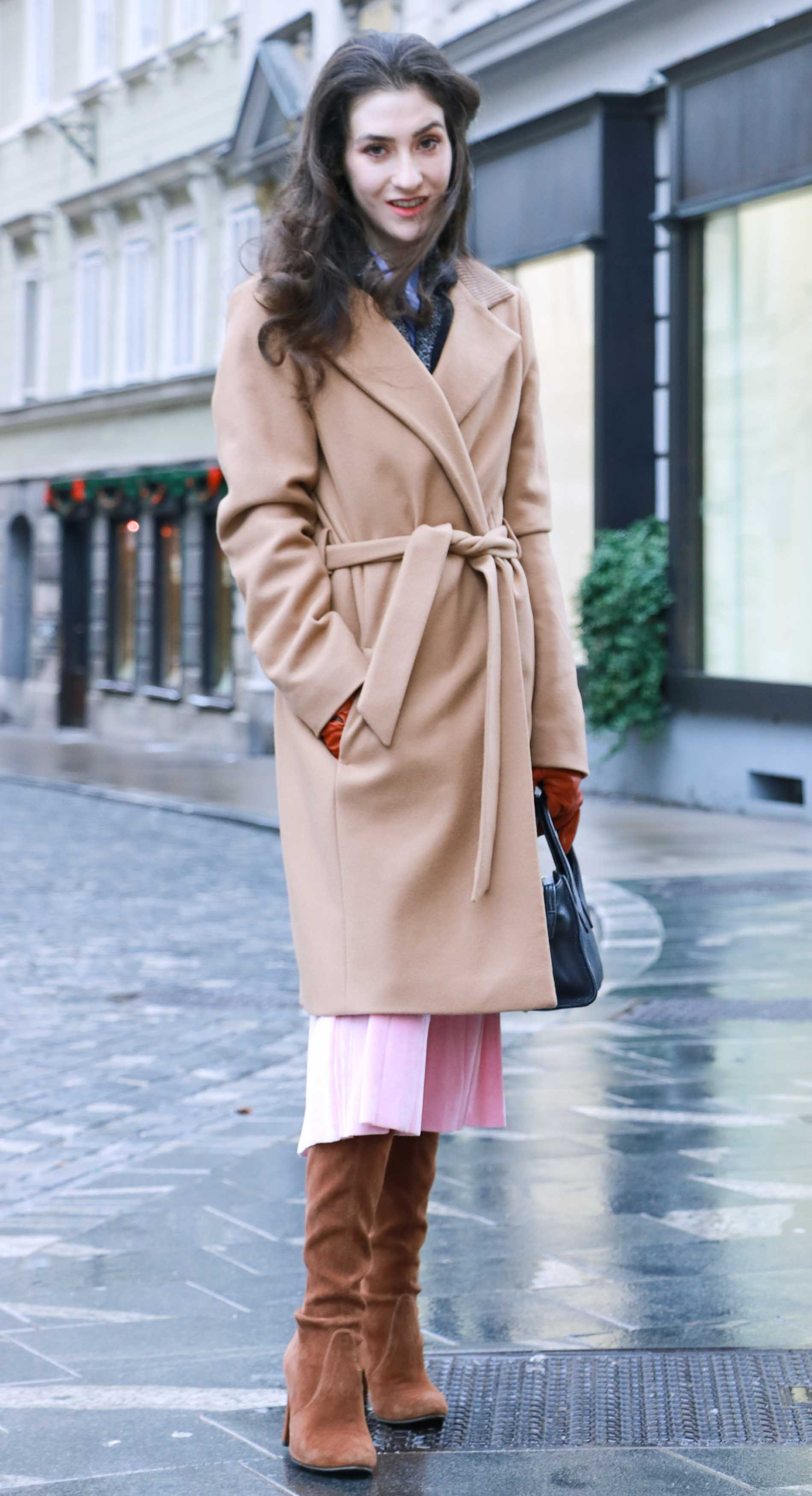 Fashion Blogger Veronika Lipar of Brunette from Wall Street wearing fashionable winter outfit, ESCADA wrap camel coat, pink velvet midi pleated skirt, brown Stuart Weitzman Highland OTK boots, black top handle bag, leather gloves on the streets of Ljubljana
