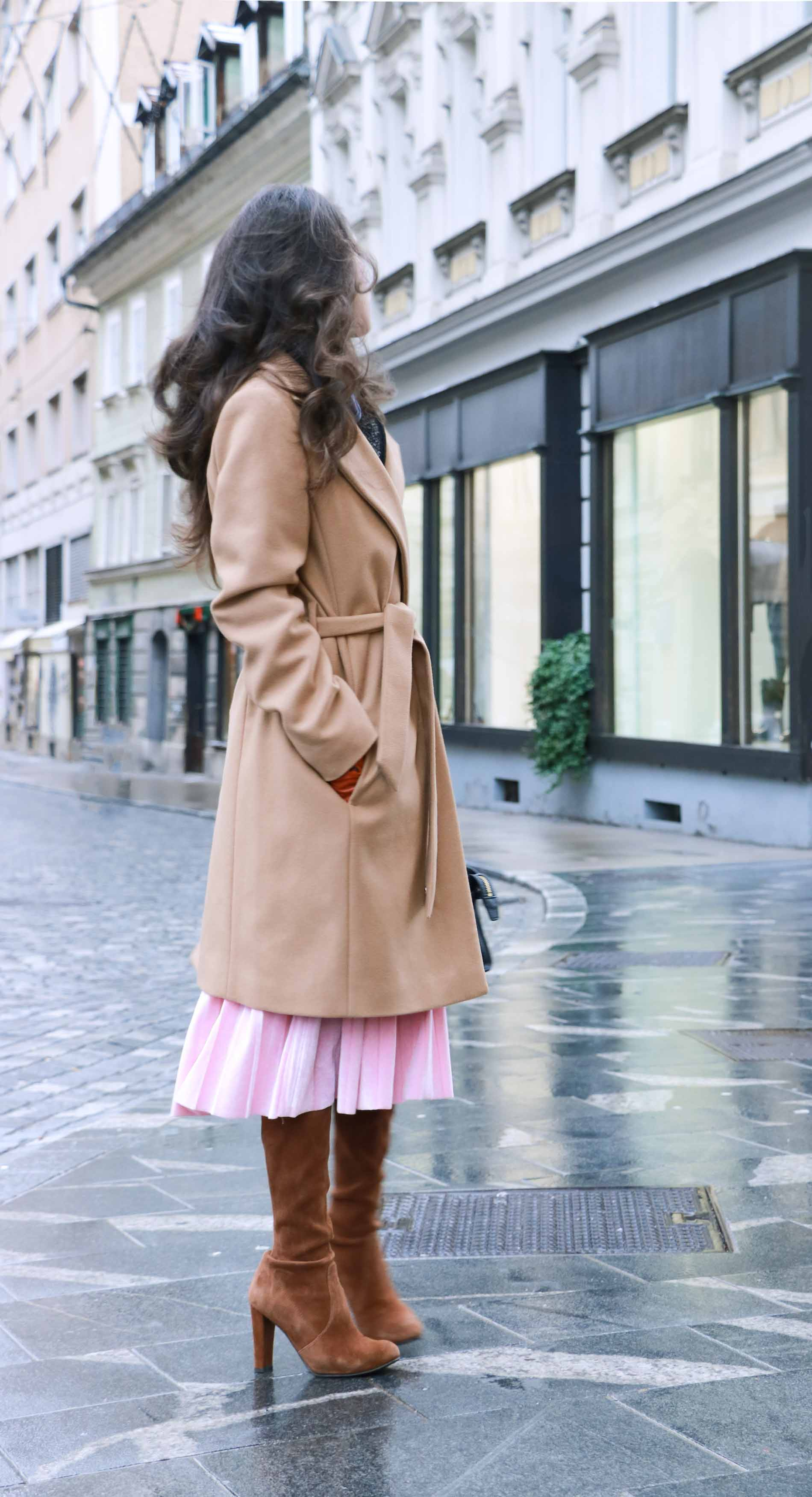 Fashion Blogger Veronika Lipar of Brunette from Wall Street wearing winter outfit, ESCADA wrap camel coat, pink velvet midi pleated skirt, brown Stuart Weitzman Highland OTK boots, black top handle bag, leather gloves, when doing Christmas shopping