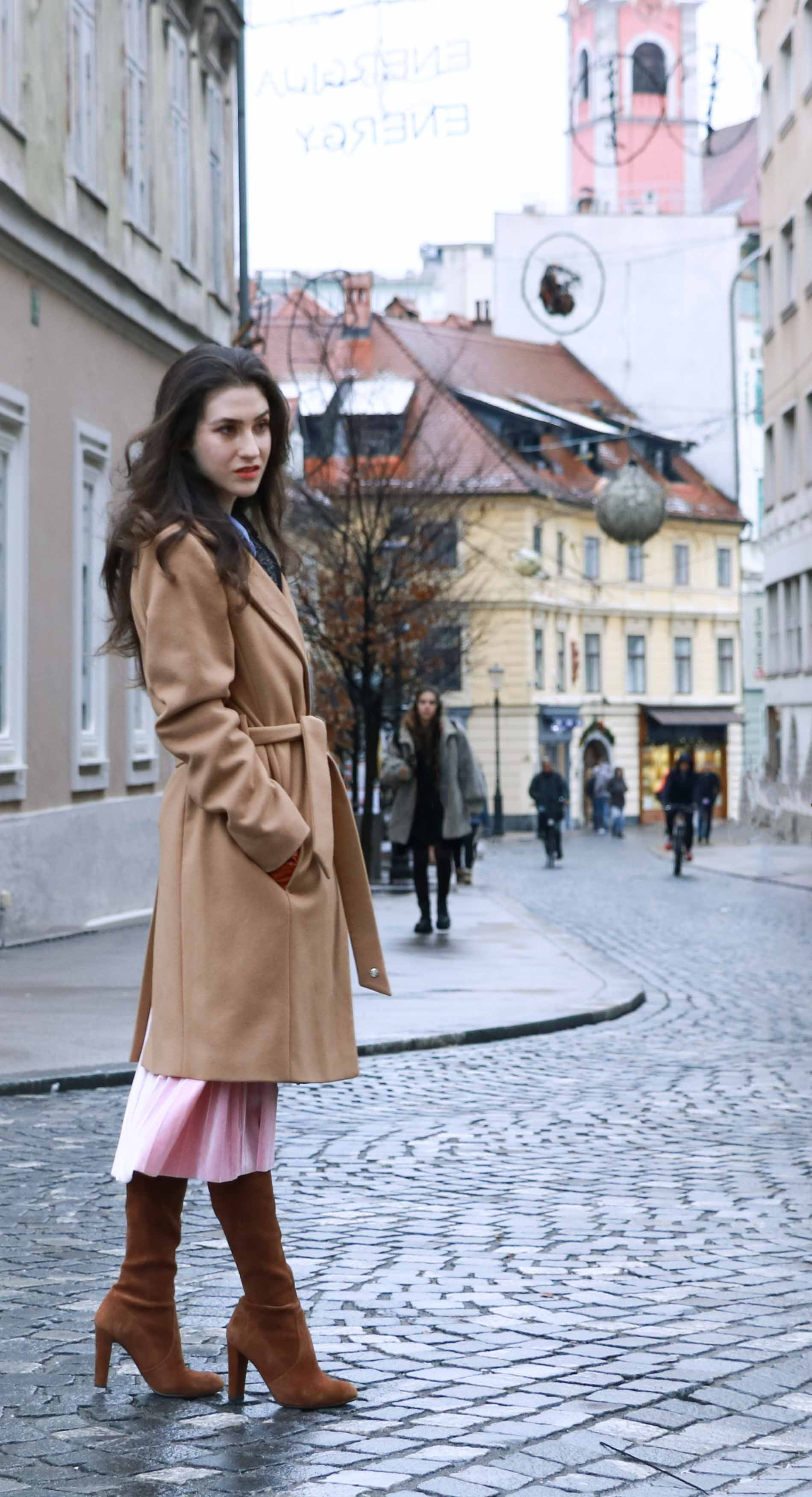 Fashion Blogger Veronika Lipar of Brunette from Wall Street wearing ESCADA wrap camel coat, pink velvet midi pleated skirt, brown Stuart Weitzman Highland OTK boots, black top handle bag, leather gloves