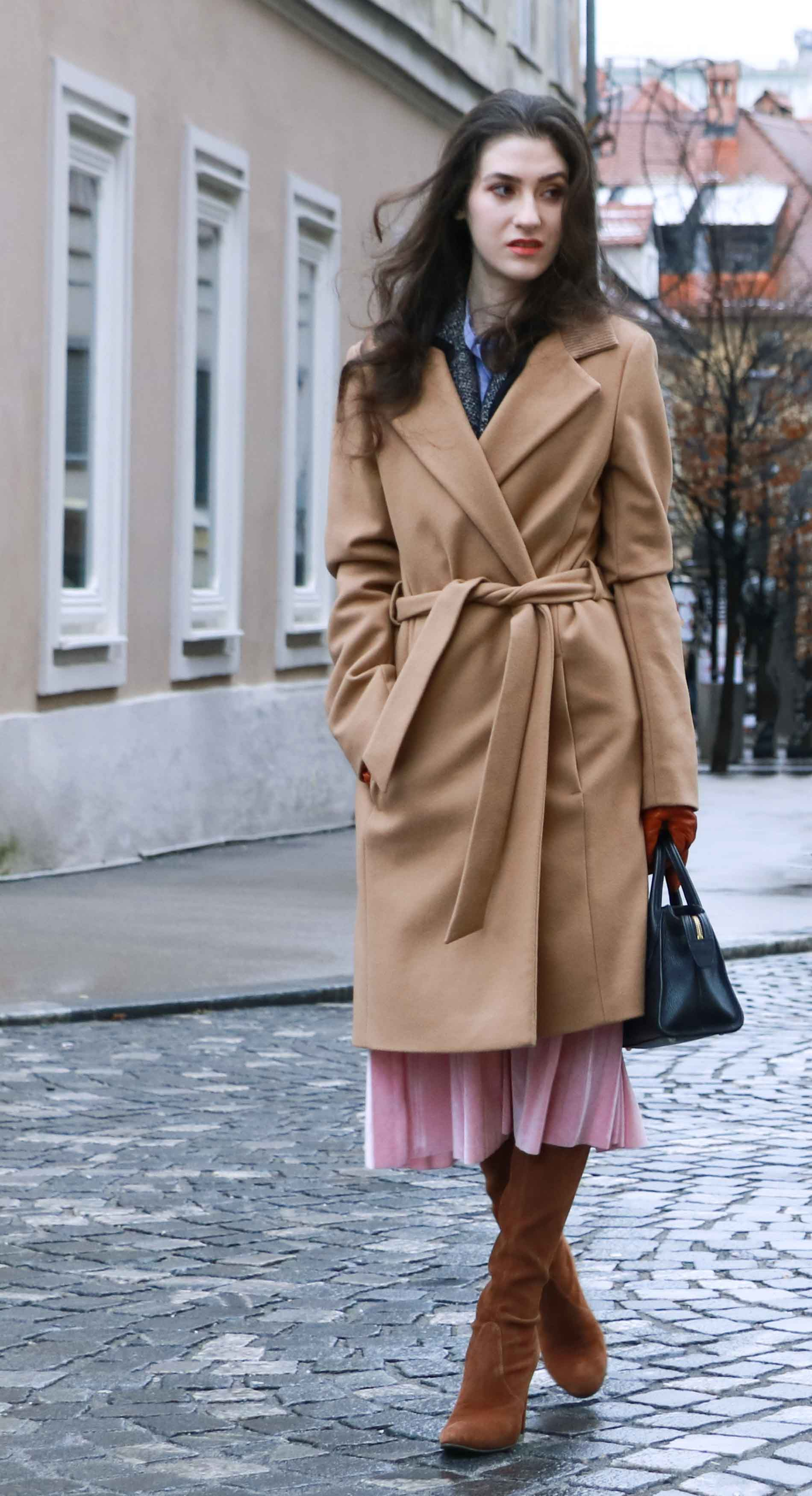 Fashion Blogger Veronika Lipar of Brunette from Wall Street dressed stylish outfit, ESCADA wrap camel coat, pink velvet midi pleated skirt, brown Stuart Weitzman Highland OTK boots, black top handle bag, leather gloves on the streets of Ljubljana