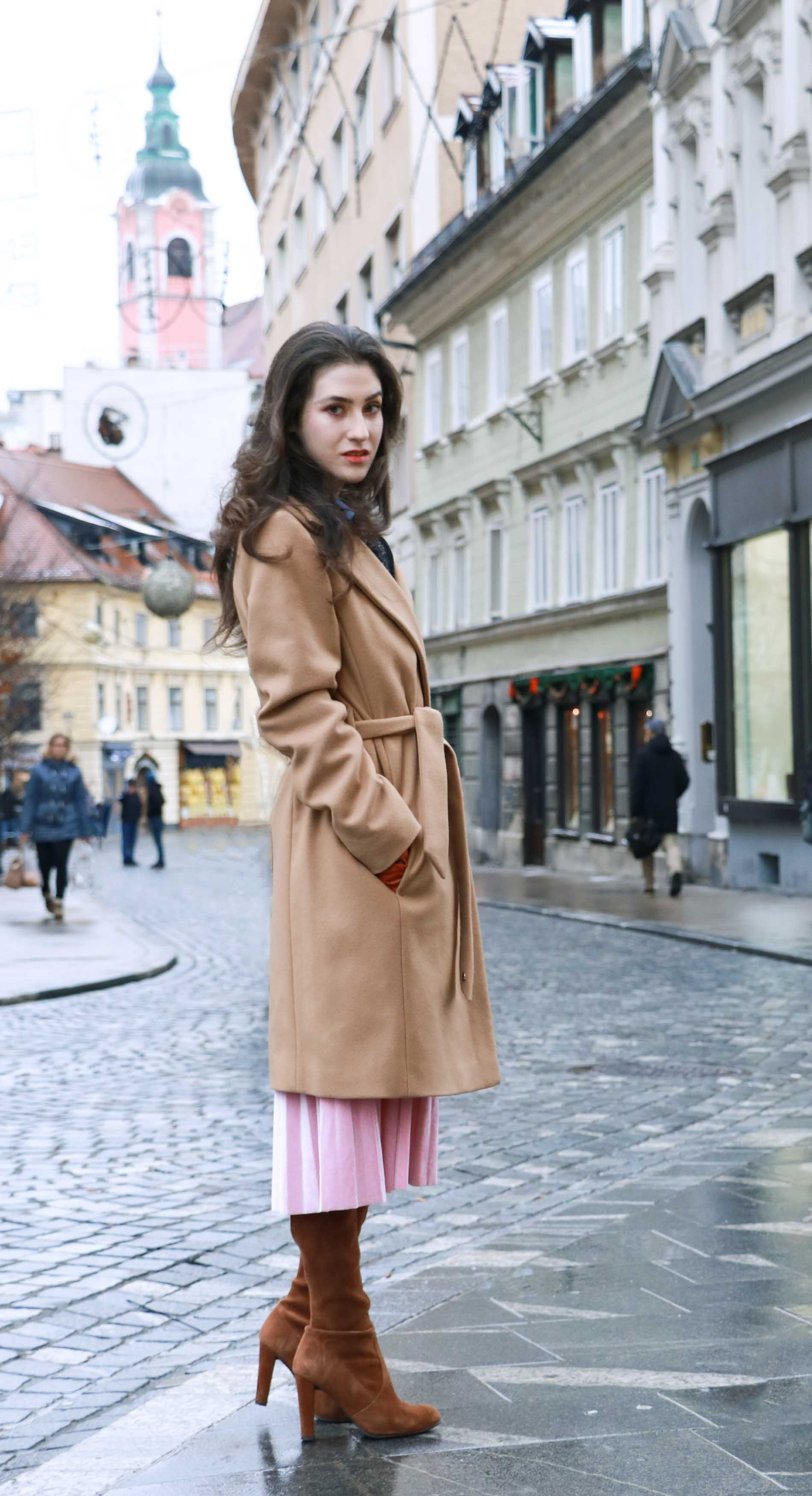 Fashion Blogger Veronika Lipar of Brunette from Wall Street wearing elegant winter outfit, ESCADA wrap camel coat, pink velvet midi pleated skirt, brown Stuart Weitzman Highland OTK boots, black top handle bag, leather gloves this Christmas