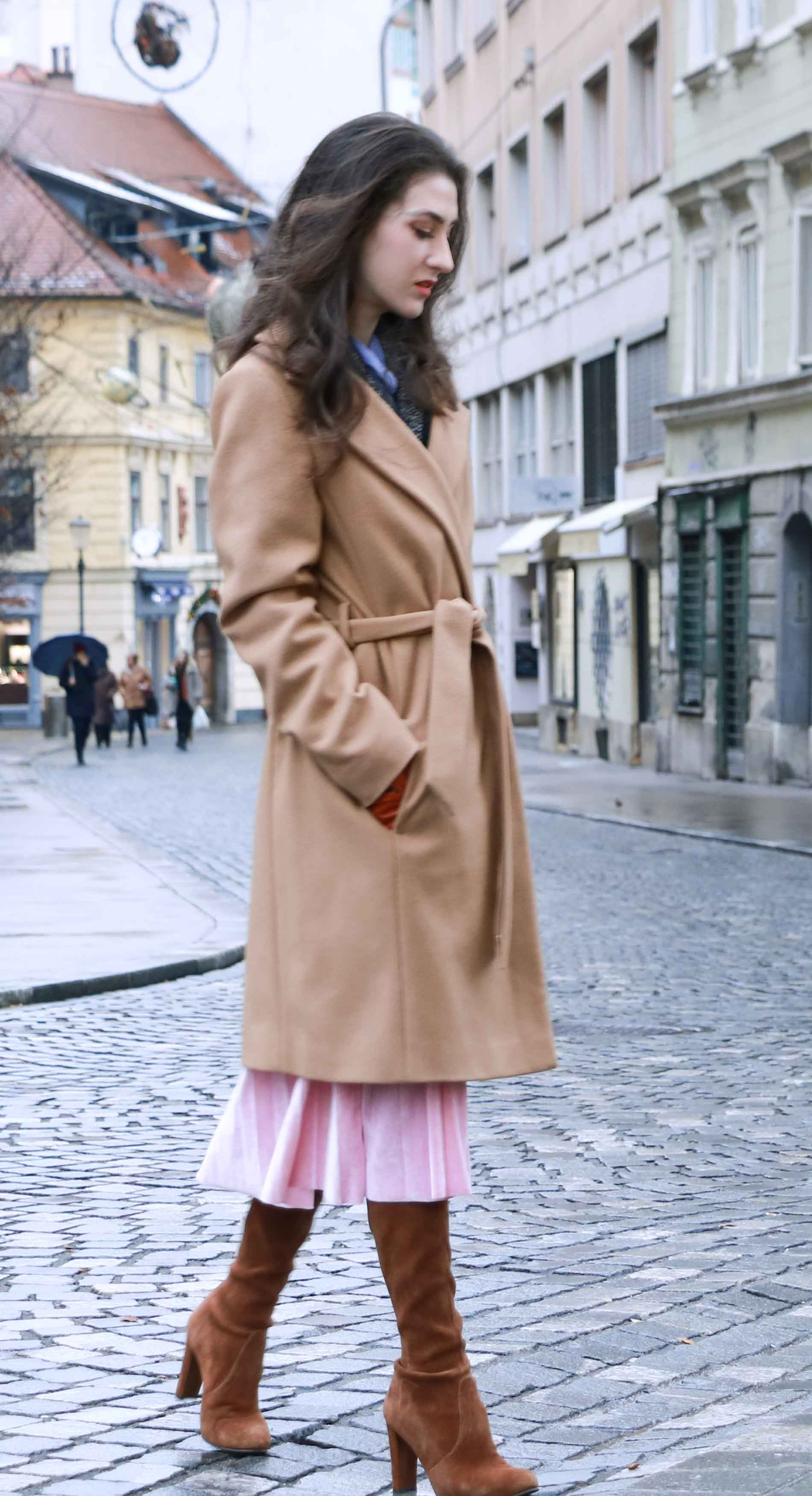 Fashion Blogger Veronika Lipar of Brunette from Wall Street dressed stylish outfit, ESCADA wrap camel coat, pink velvet midi pleated skirt, brown Stuart Weitzman Highland over the knee boots, black top handle bag, leather gloves on the streets of Ljubljana