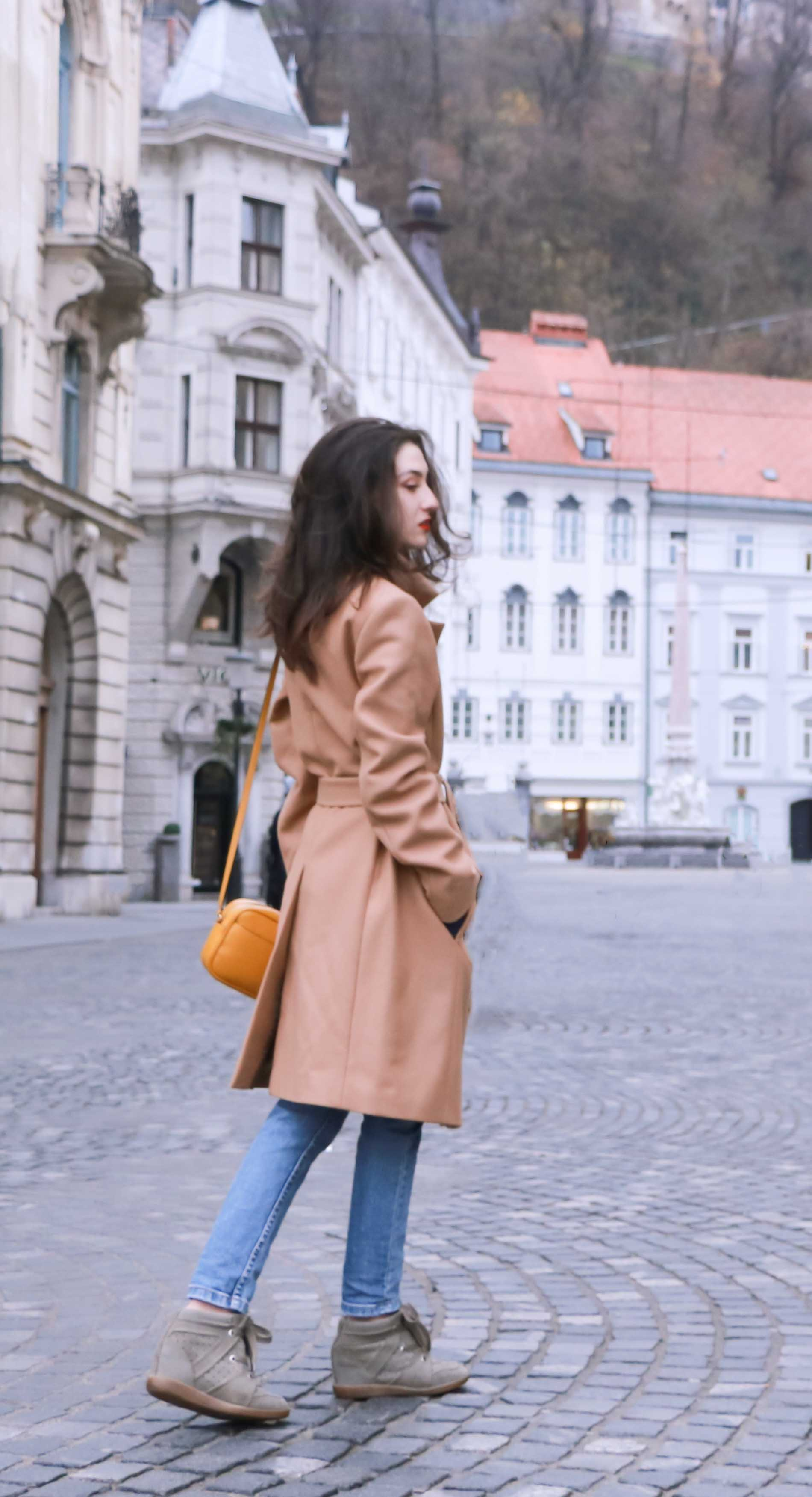 Fashion Blogger Veronika Lipar of Brunette from Wall Street wearing casual outfit, ESCADA wrap camel coat, A.P.C. blue jeans, Isabel Marant olive Bobby Sneakers, yellow shoulder bag from Escada, white Victorian blouse on the streets of Ljubljana