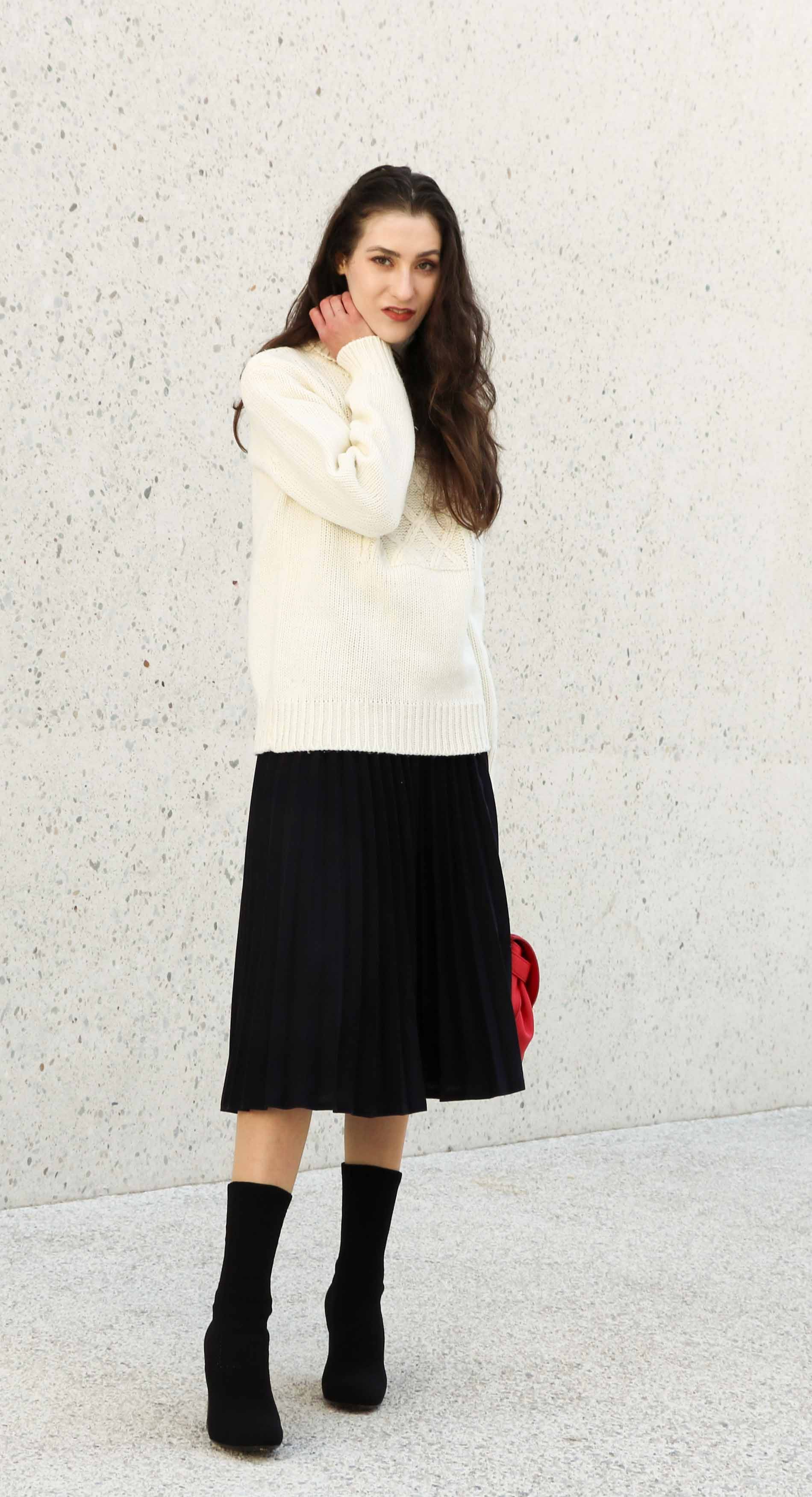Fashion Blogger Veronika Lipar of Brunette from Wall Street wearing white oversized cable knit sweater, black pleated midi skirt, pink top handle bag from See by Chloe and black sock boots from Elena Iachi