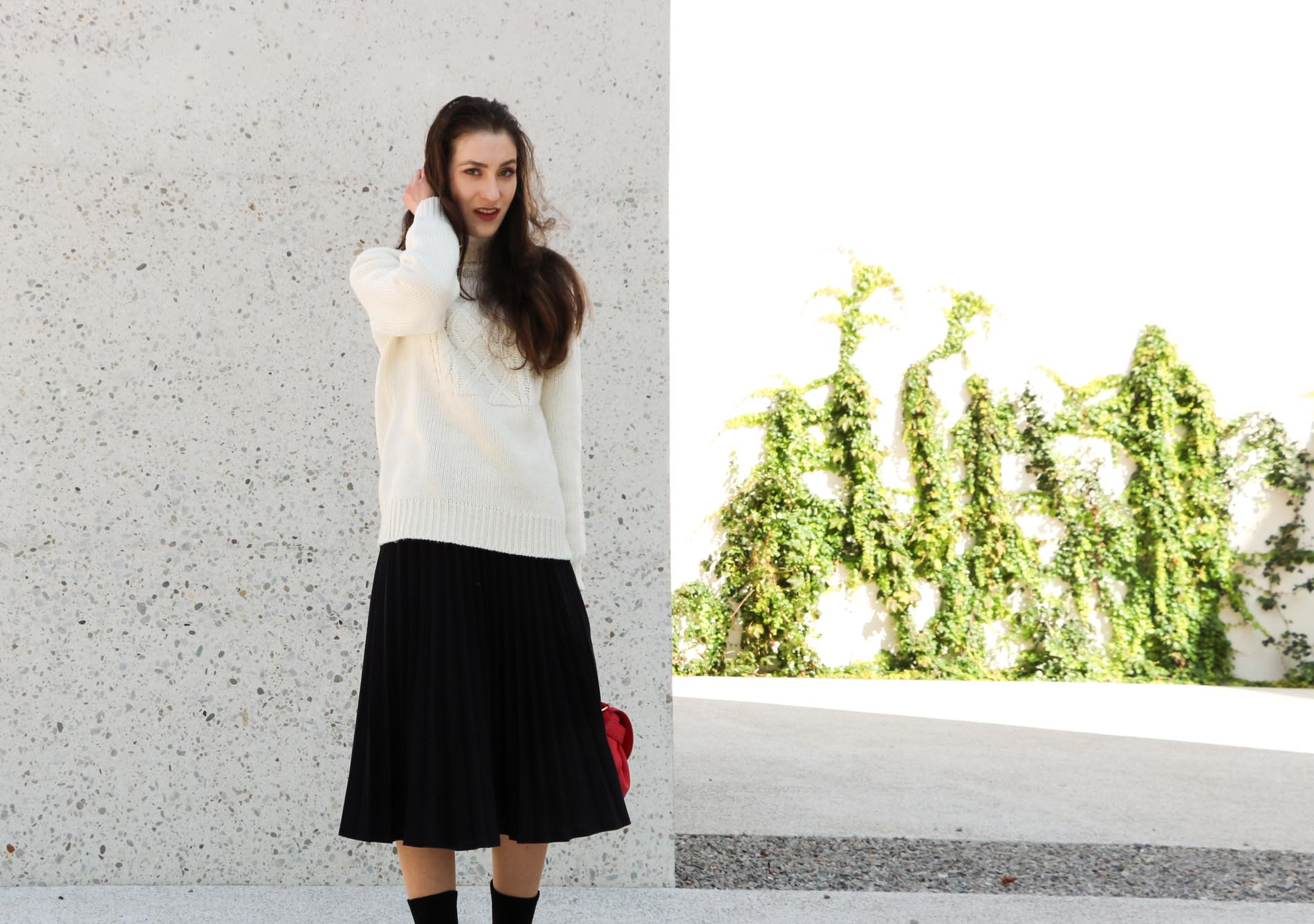 Fashion Blogger Veronika Lipar of Brunette from Wall Street wearing white oversized turtleneck sweater, black midi skirt with pleats, pink top handle bag from See by Chloe and black sock boots from Elena Iachi in winter