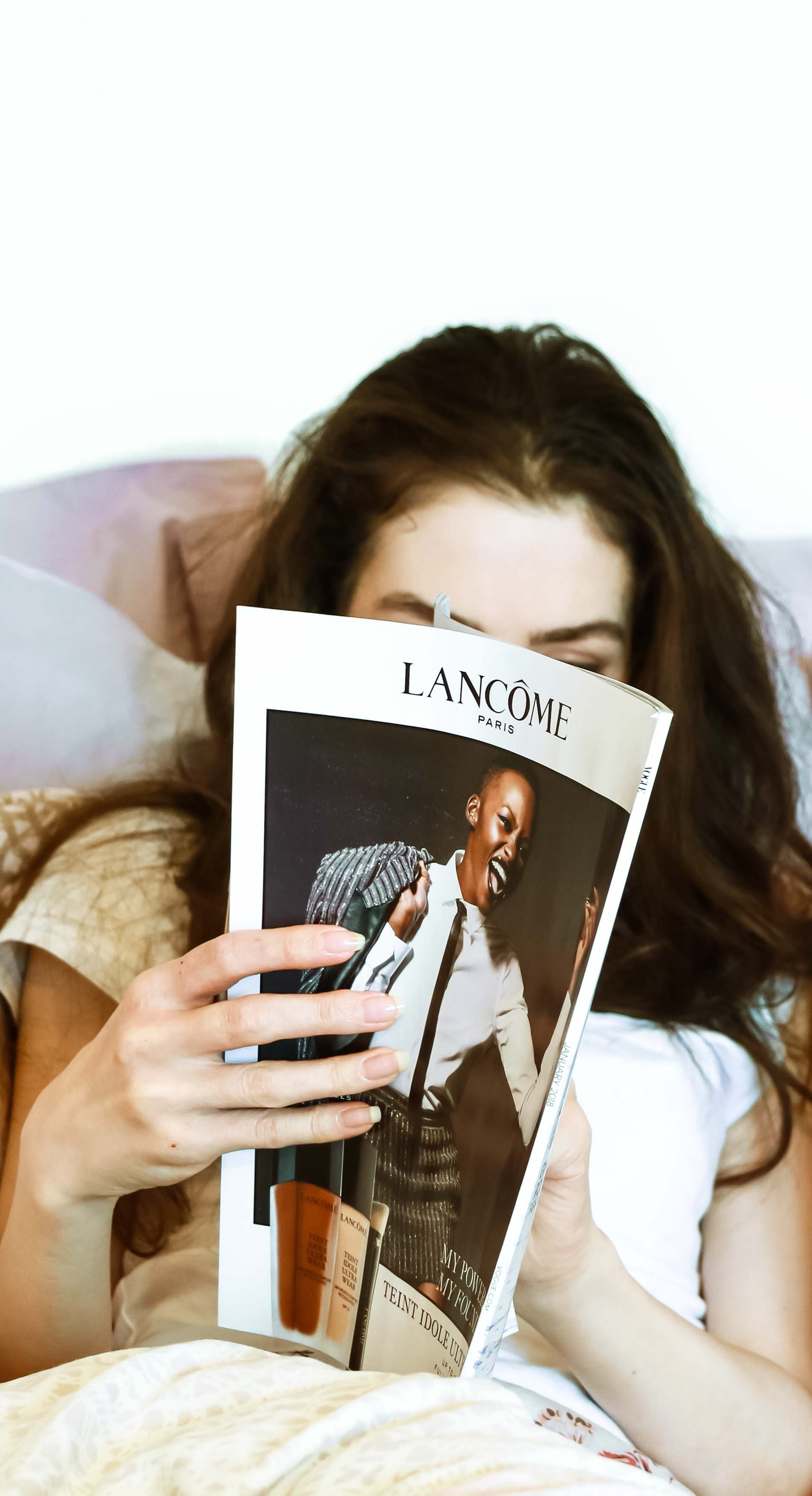 Fashion Blogger Veronika Lipar of Brunette from Wall Street reading Vogue magazine in bed