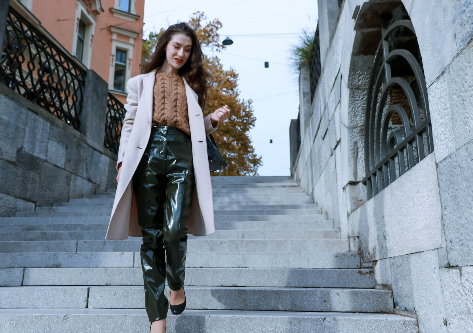 Fashion Blogger Veronika Lipar of Brunette from Wall Street dressed in Acne Studios high-shine pants, Weekened Maxmara double breasted pastel coat, Max Mara camel cable knit sweater and black Aquazzura pumps while walking down the stairs