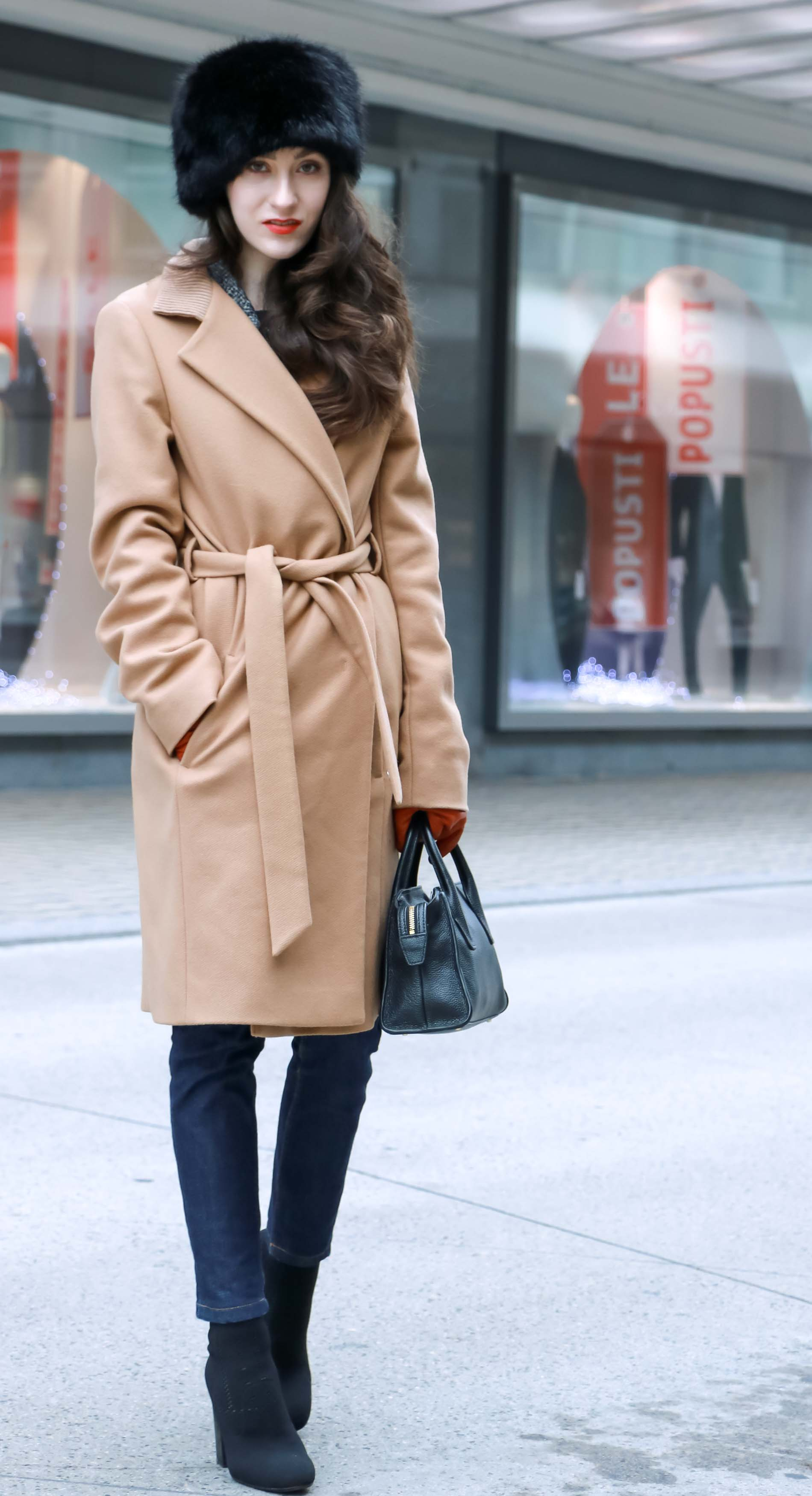 Veronika Lipar of Brunette from Wall Street wearing wrap Escada camel coat, A.P.C. dark tapered denim jeans, black sock boots from Elena Iachi, black fur hat and small black top handle bag while standing the street
