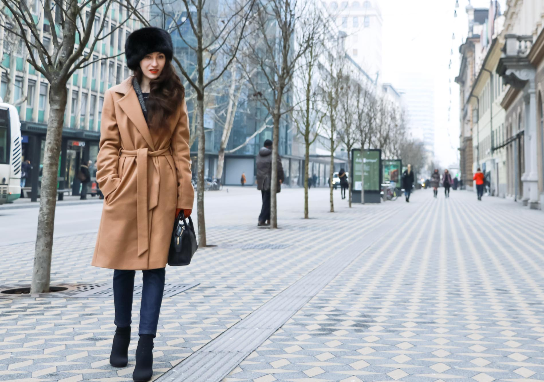 Veronika Lipar of Brunette from Wall Street wearing wrap Escada camel coat, A.P.C. dark tapered denim jeans, black sock boots from Elena Iachi, black fur hat and small black top handle bag while walking down the street