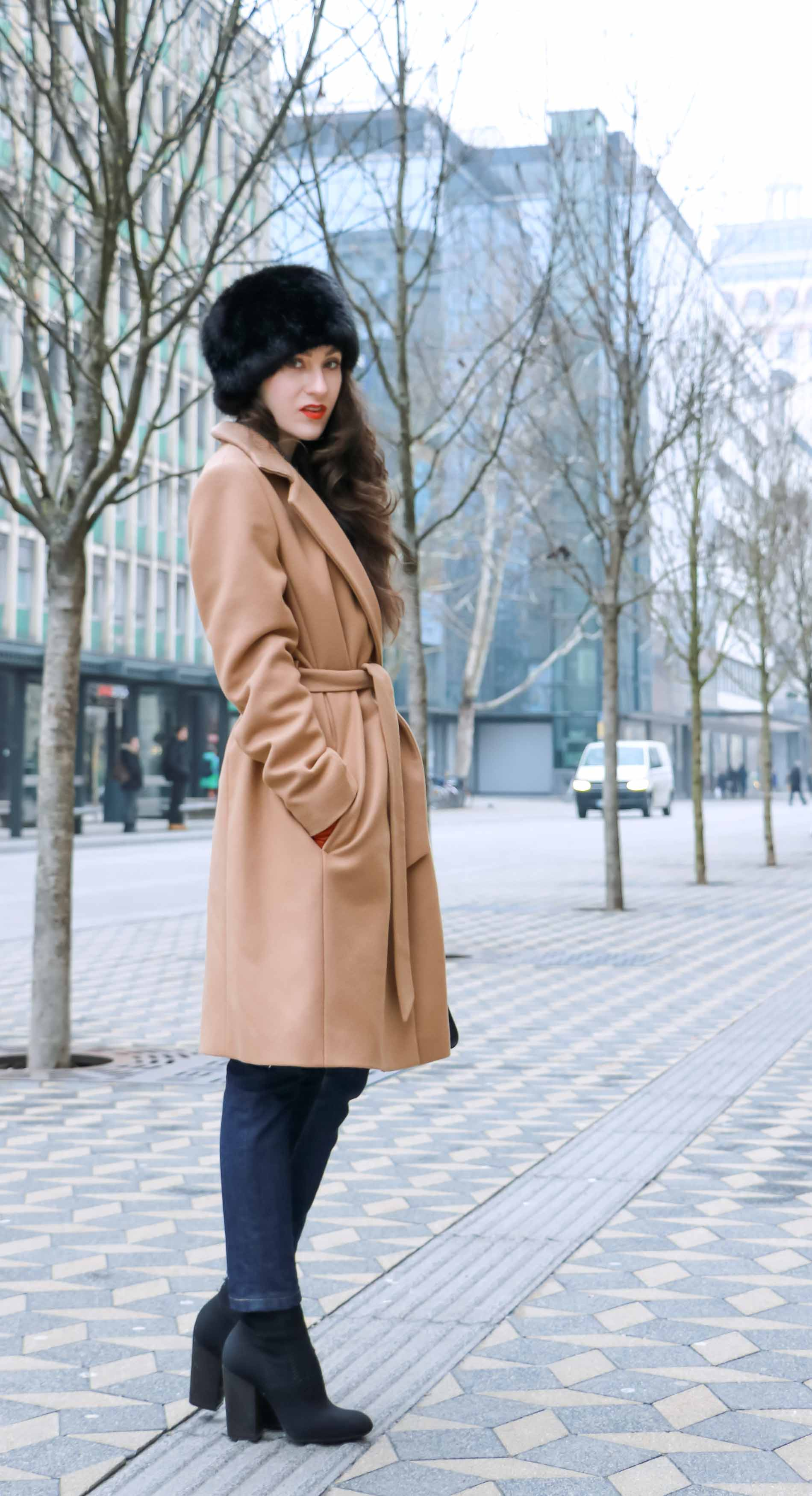Veronika Lipar of Brunette from Wall Street dressed in wrap Escada camel coat, A.P.C. dark tapered denim jeans, black sock boots from Elena Iachi, black fur hat and small black top handle bag while standing the street