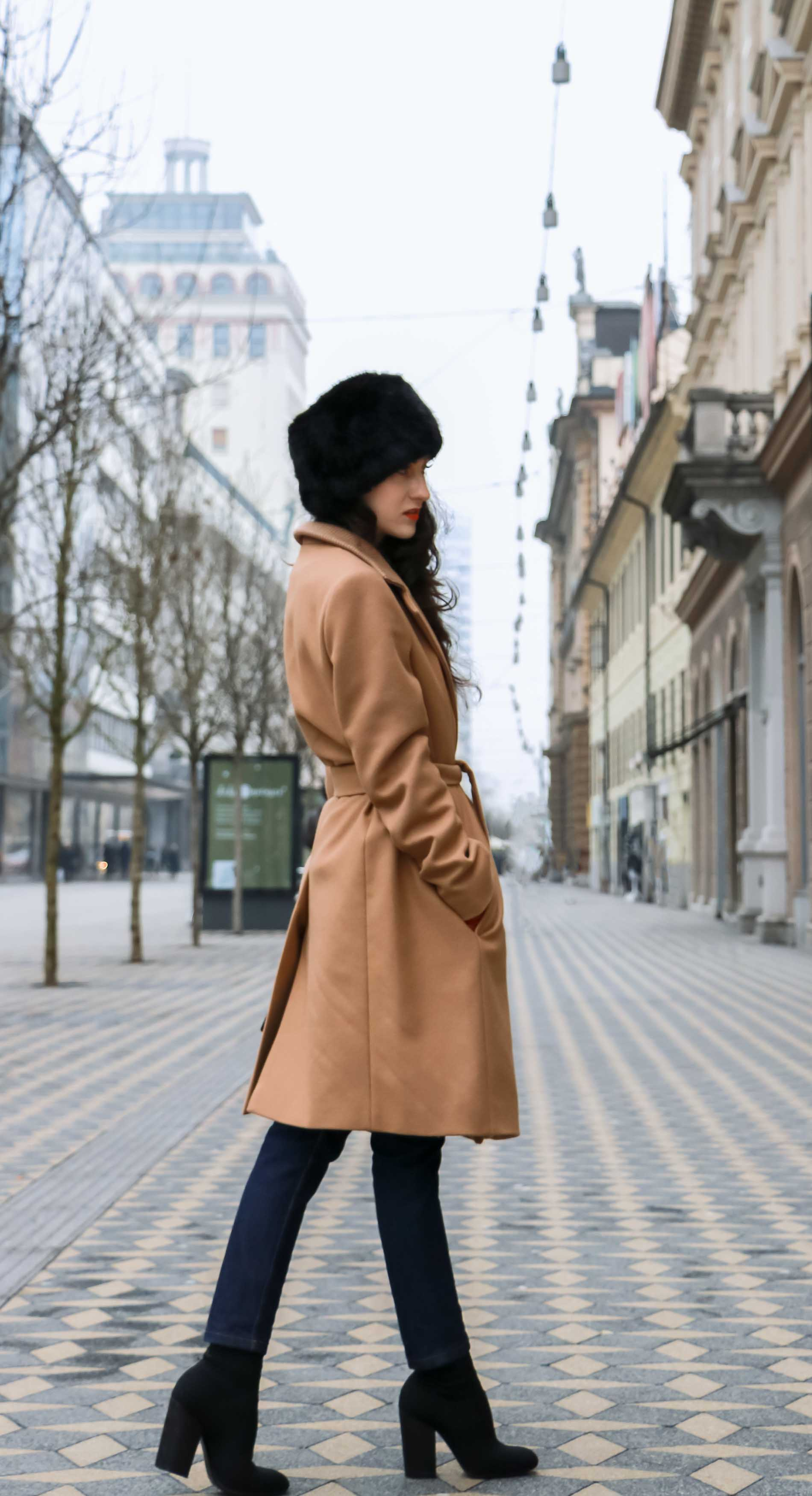 Veronika Lipar of Brunette from Wall Street wearing wrap Escada camel coat, A.P.C. dark tapered denim jeans, black sock boots from Elena Iachi, black fur hat and small black top handle bag while walking on the street