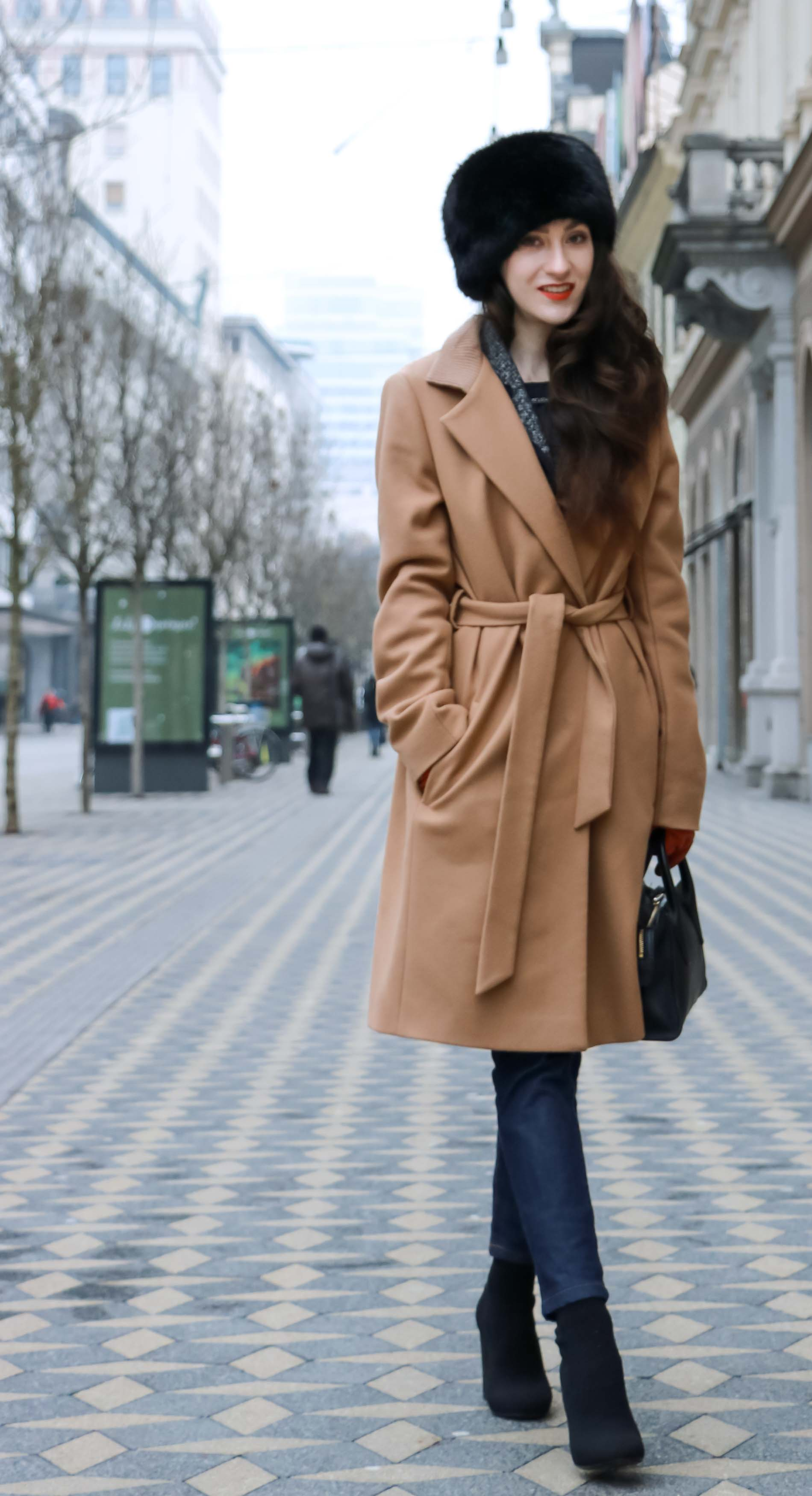 Fashion Blogger Veronika Lipar of Brunette from Wall Street wearing wrap Escada camel coat, A.P.C. dark tapered denim jeans, black sock boots from Elena Iachi, black fur hat and small black top handle bag while walking down the street