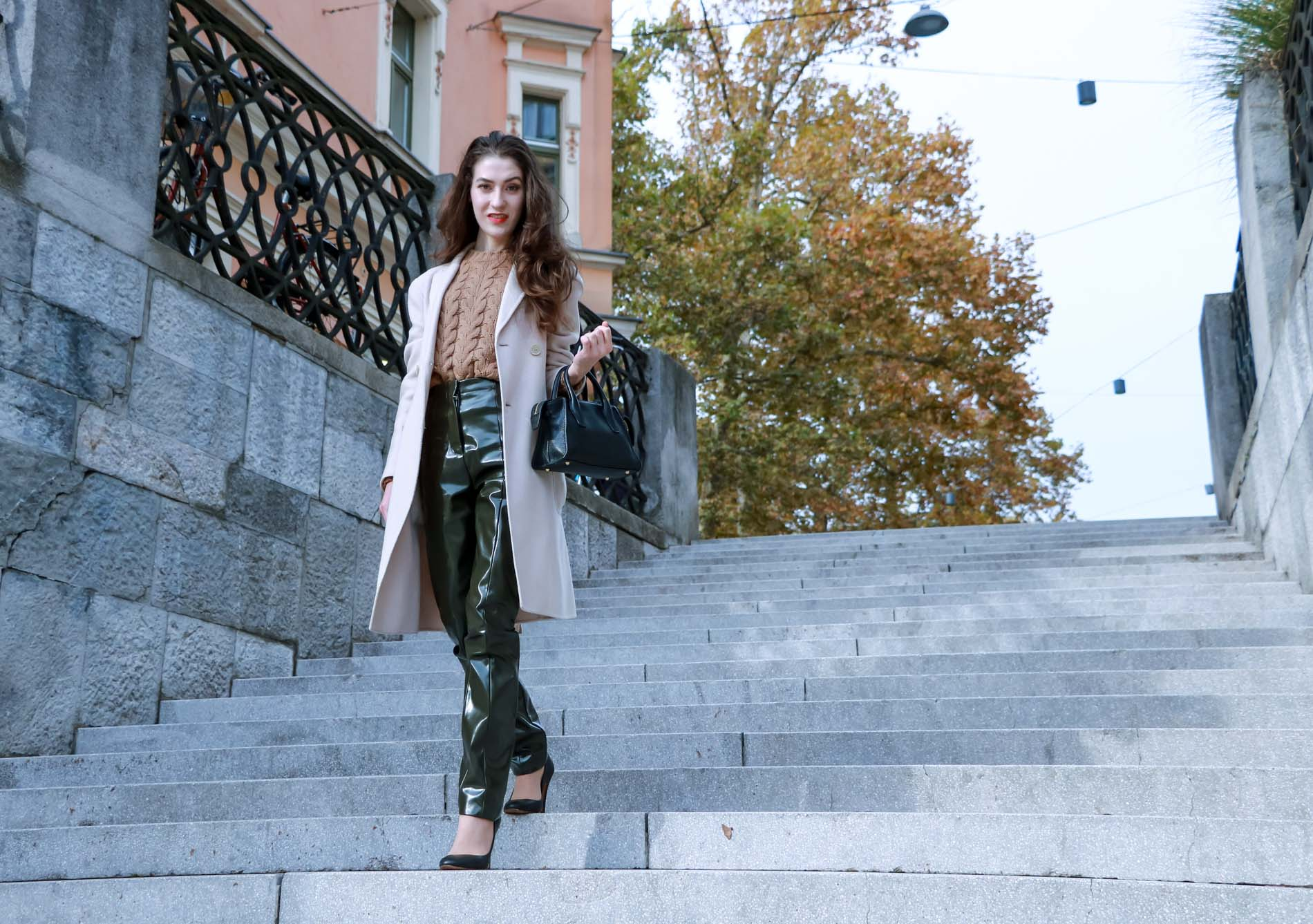 Fashion Blogger Veronika Lipar of Brunette from Wall Street dressed in Acne Studios high-shine pants, Weekened Maxmara double breasted pastel coat, Max Mara camel cable knit sweater and black Aquazzura pumps as chic business outfit