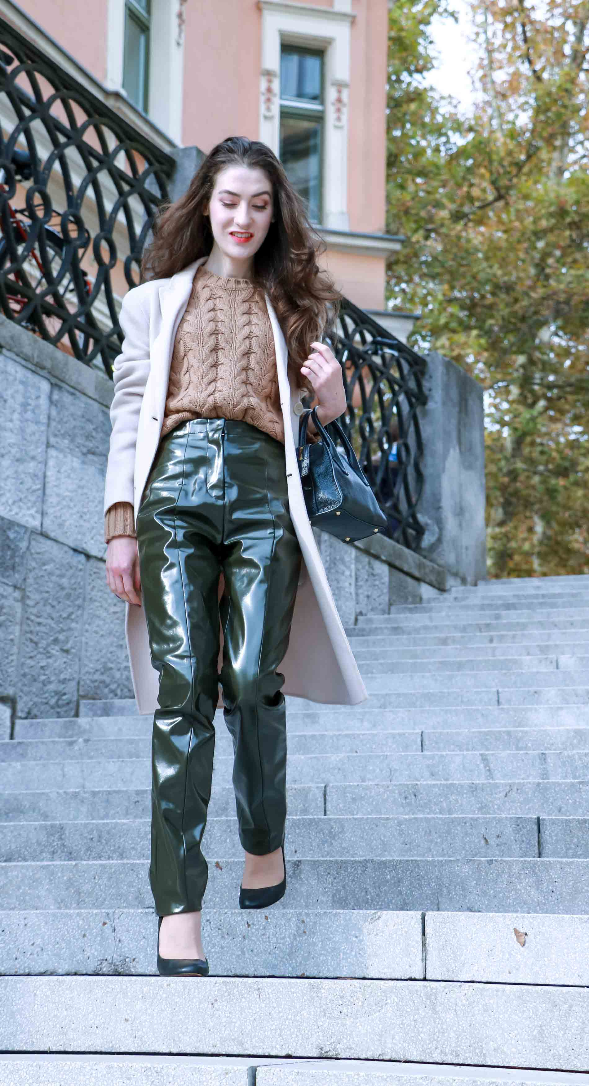 Fashion Blogger Veronika Lipar of Brunette from Wall Street dressed in Acne Studios vinyl pants, Weekened Maxmara double breasted pastel coat, Max Mara camel cable knit sweater and black Aquazzura pumps, black tote bag while walking down the stairs