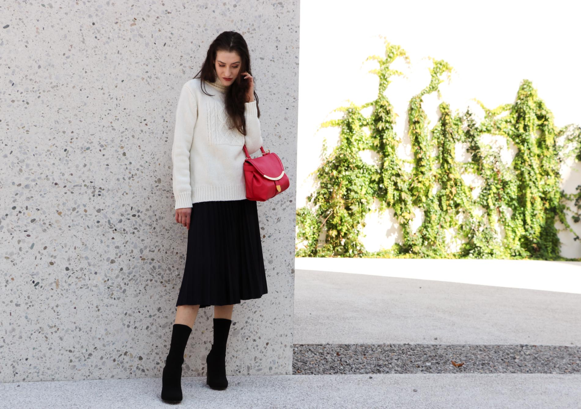 Fashion Blogger Veronika Lipar of Brunette from Wall Street dressed in white oversize cable knit sweater, black pleated midi skirt, pink top handle bag from See by Chloe and black sock boots from Elena Iachi