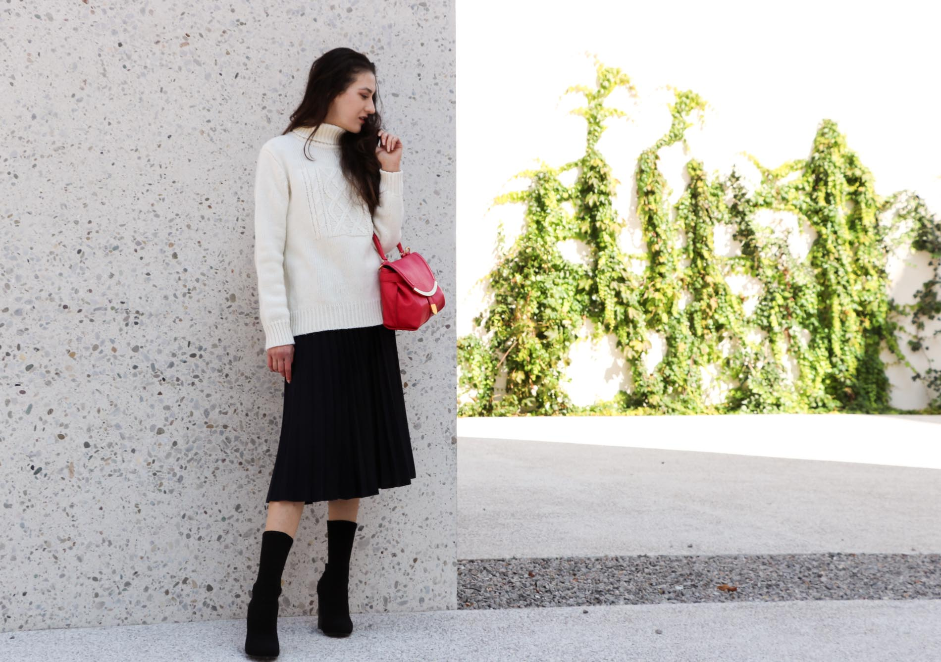 Fashion Blogger Veronika Lipar of Brunette from Wall Street dressed in white oversized cable knit sweater, black pleated midi skirt, pink top handle bag from See by Chloe and black sock boots from Elena Iachi