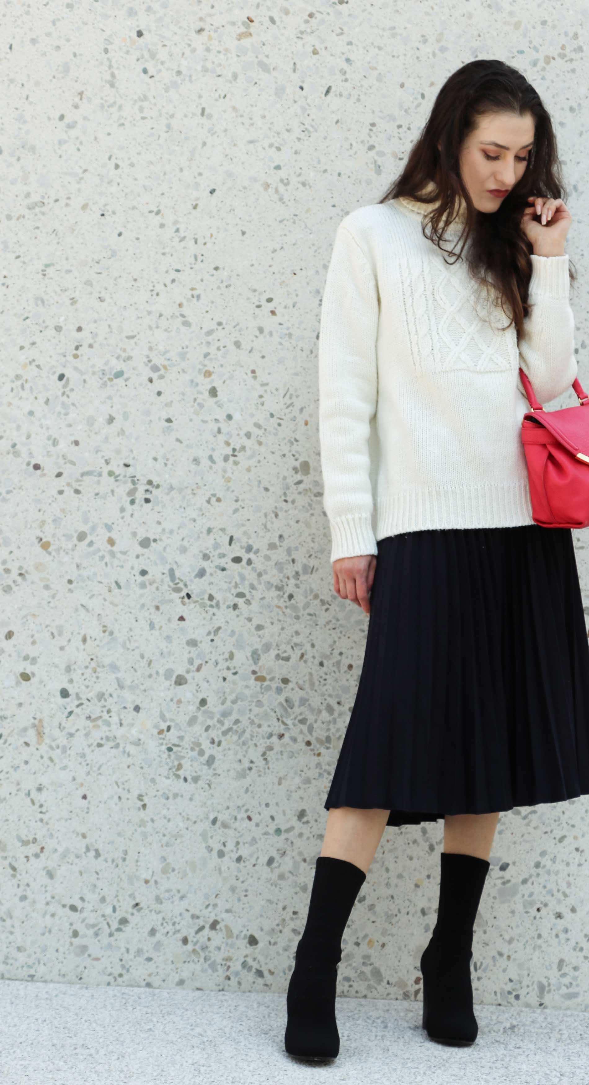 Fashion Blogger Veronika Lipar of Brunette from Wall Street wearing white oversized cable knit sweater, black midi skirt with pleats, pink top handle bag from See by Chloe and black sock boots from Elena Iachi