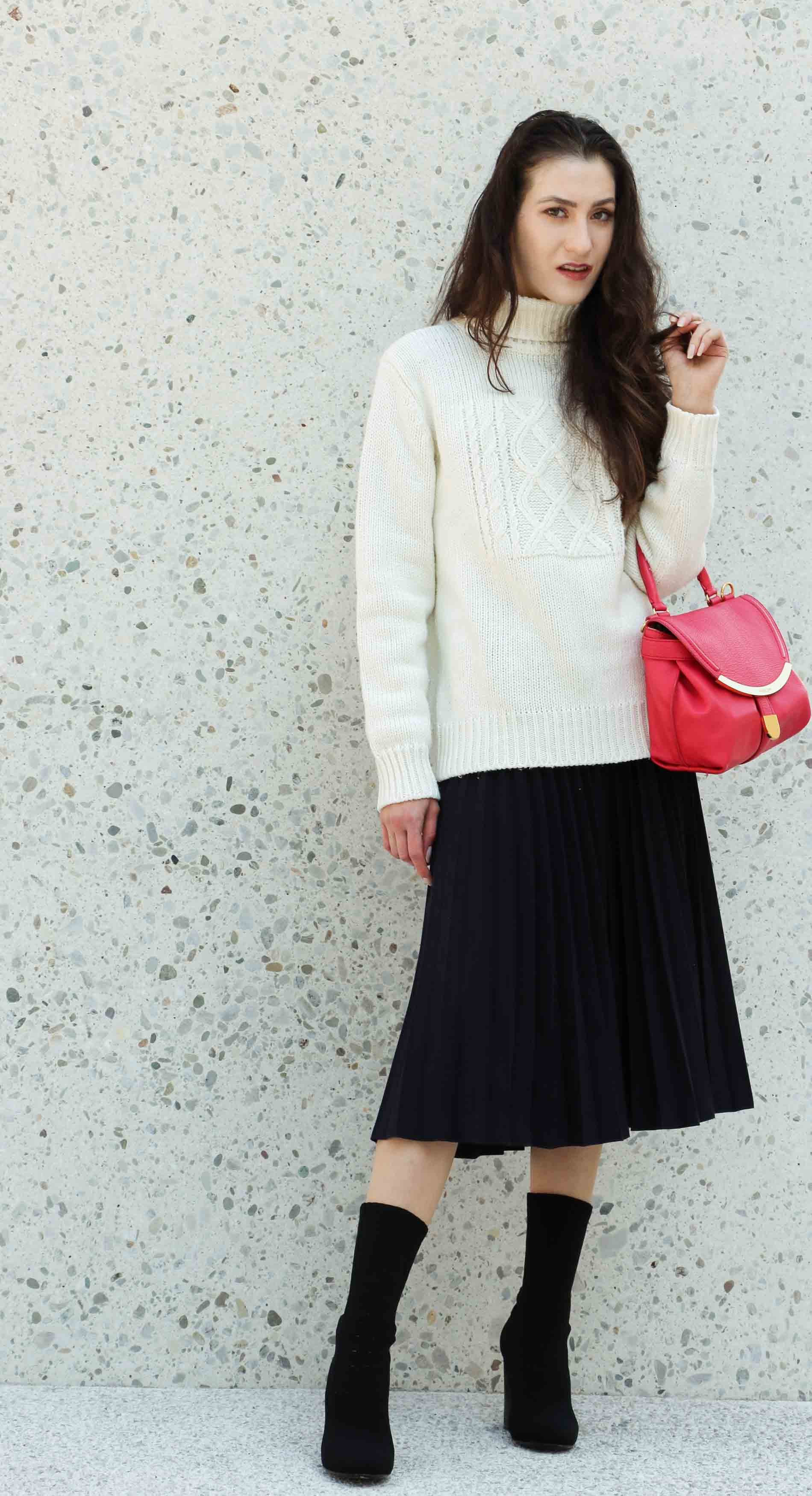 Fashion Blogger Veronika Lipar of Brunette from Wall Street wearing white oversize cable knit sweater, black pleated midi skirt, pink top handle bag from See by Chloe and black sock boots from Elena Iachi