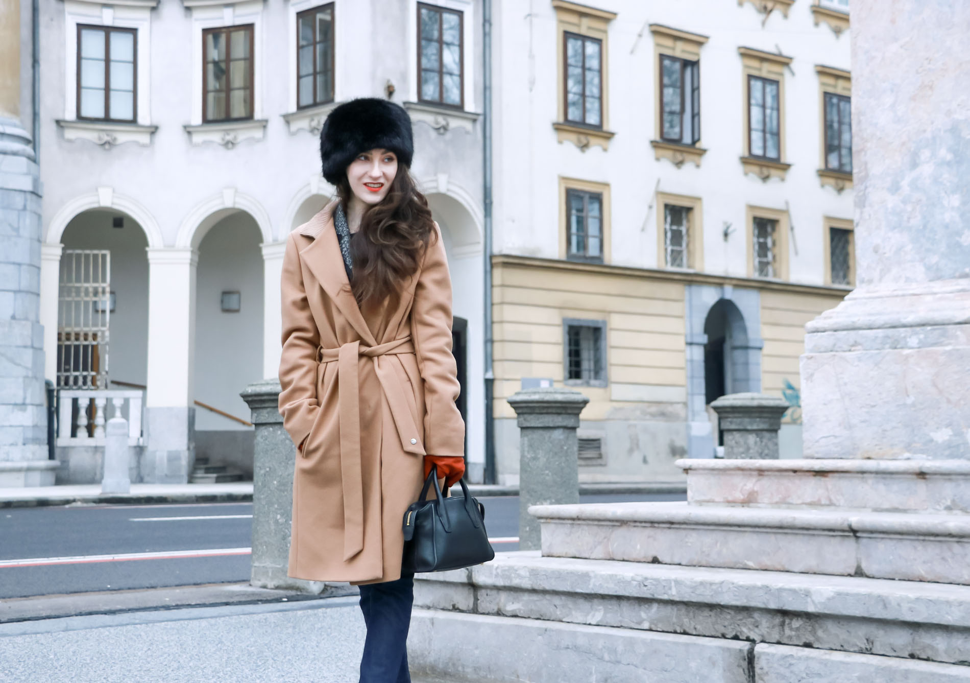 Fashion Blogger Veronika Lipar of Brunette from Wall Street dressed in wrap Escada camel coat, A.P.C. dark tapered denim jeans, black sock boots from Elena Iachi, black fur hat and small black top handle bag