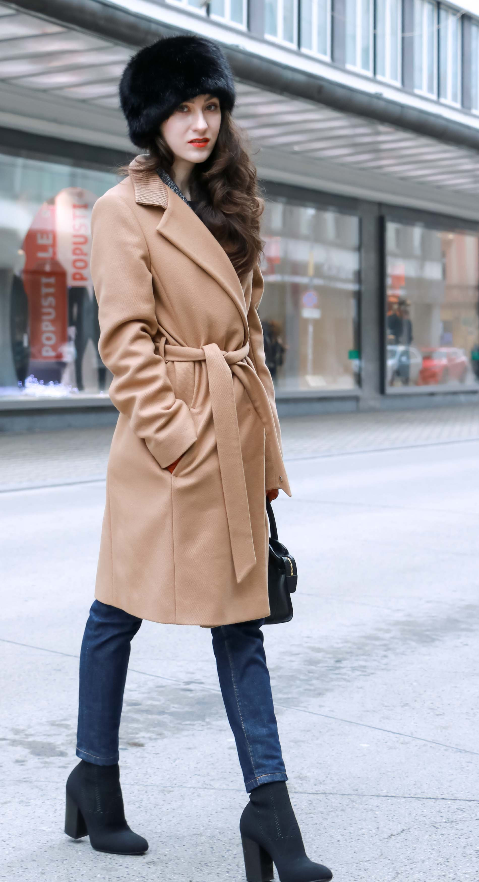 Veronika Lipar of Brunette from Wall Street wearing wrap Escada camel coat, A.P.C. dark tapered denim jeans, black sock boots from Elena Iachi, black fur hat and small black top handle bag while crossing street in Ljubljana
