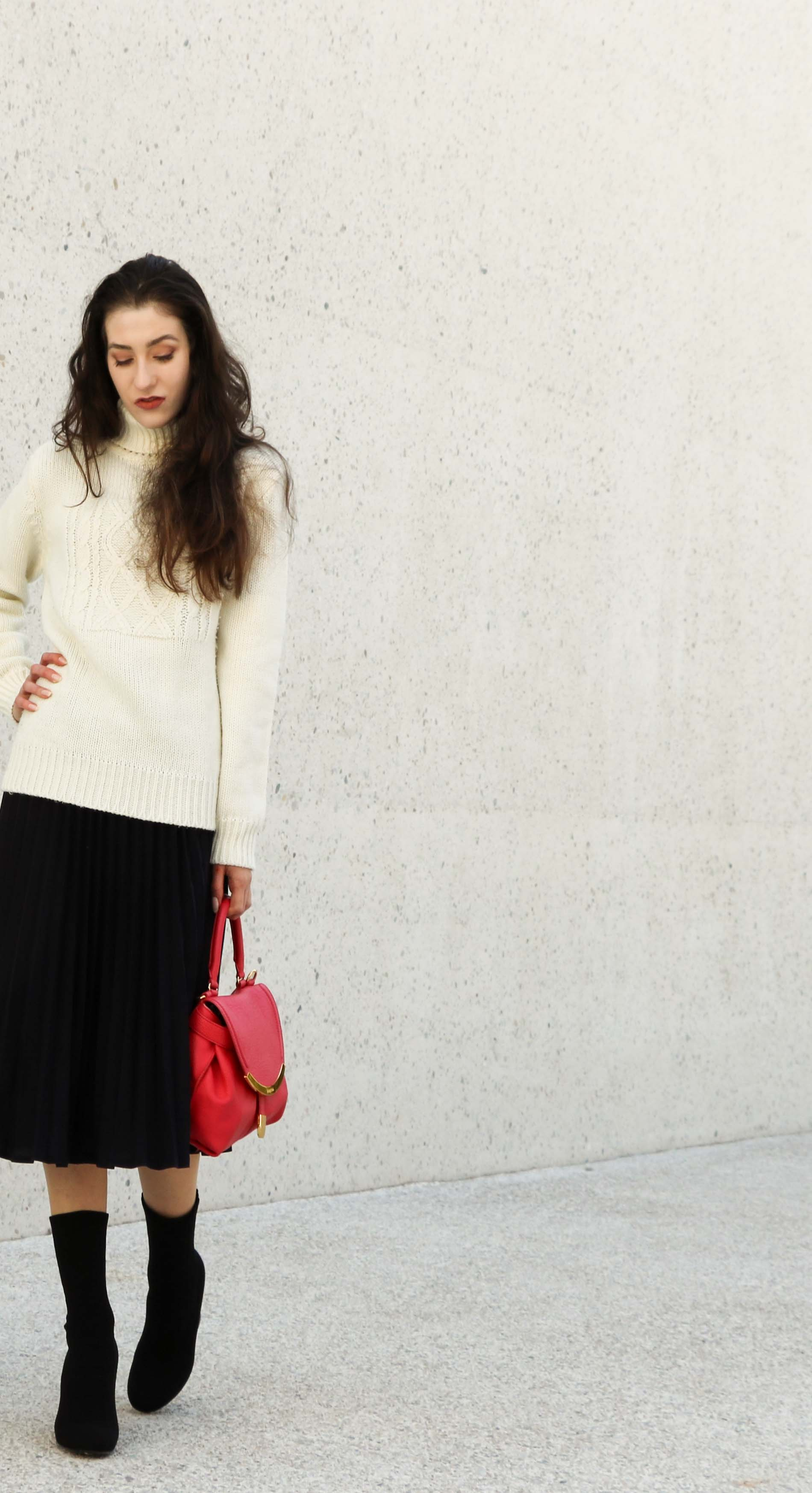 Fashion Blogger Veronika Lipar of Brunette from Wall Street dressed in white oversized cable knit sweater, black midi skirt with pleats, pink top handle bag from See by Chloe and black sock boots from Elena Iachi