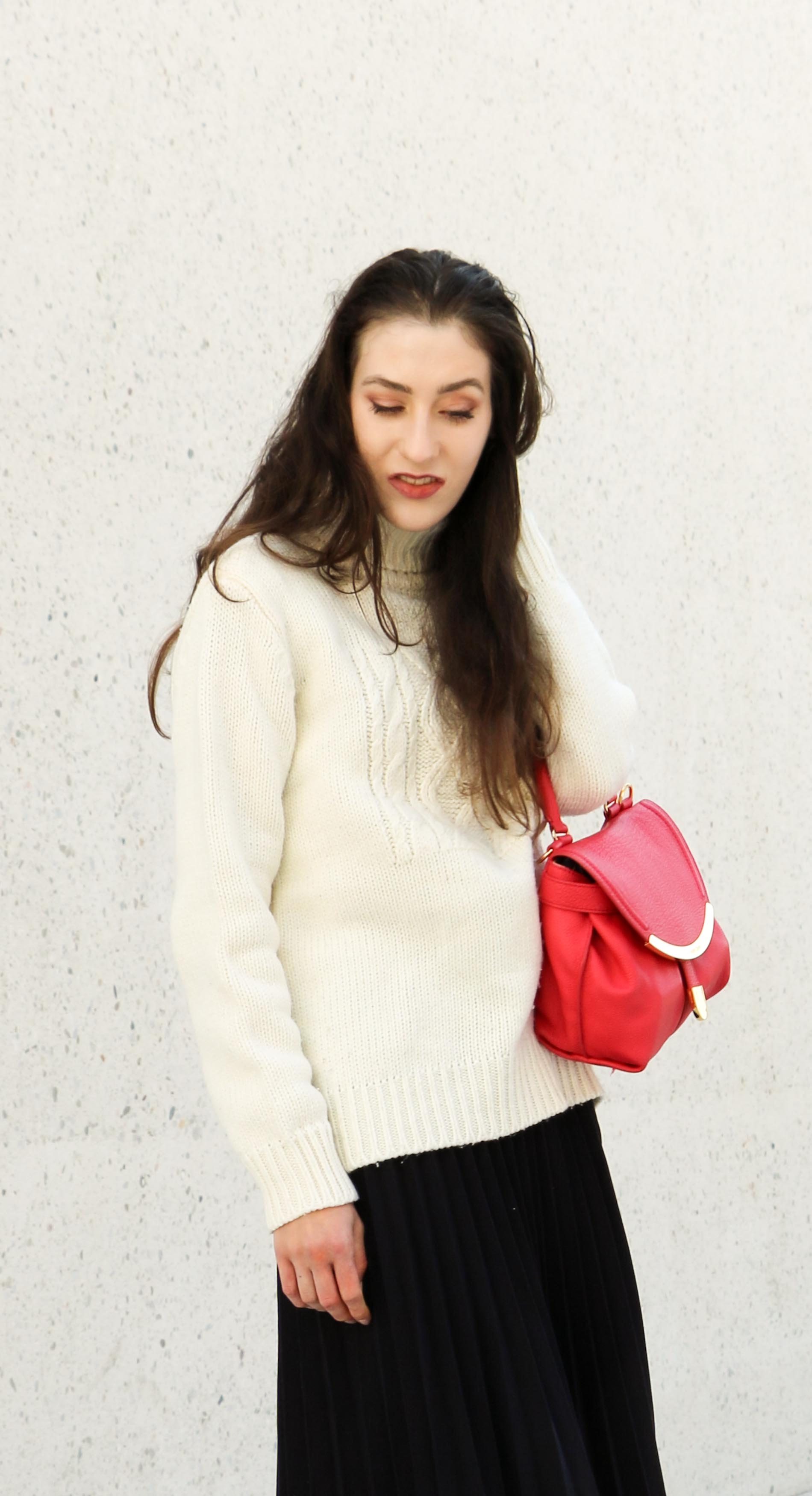 Fashion Blogger Veronika Lipar of Brunette from Wall Street dressed in white oversized cable knit sweater, black pleated midi skirt, pink top handle bag from See by Chloe