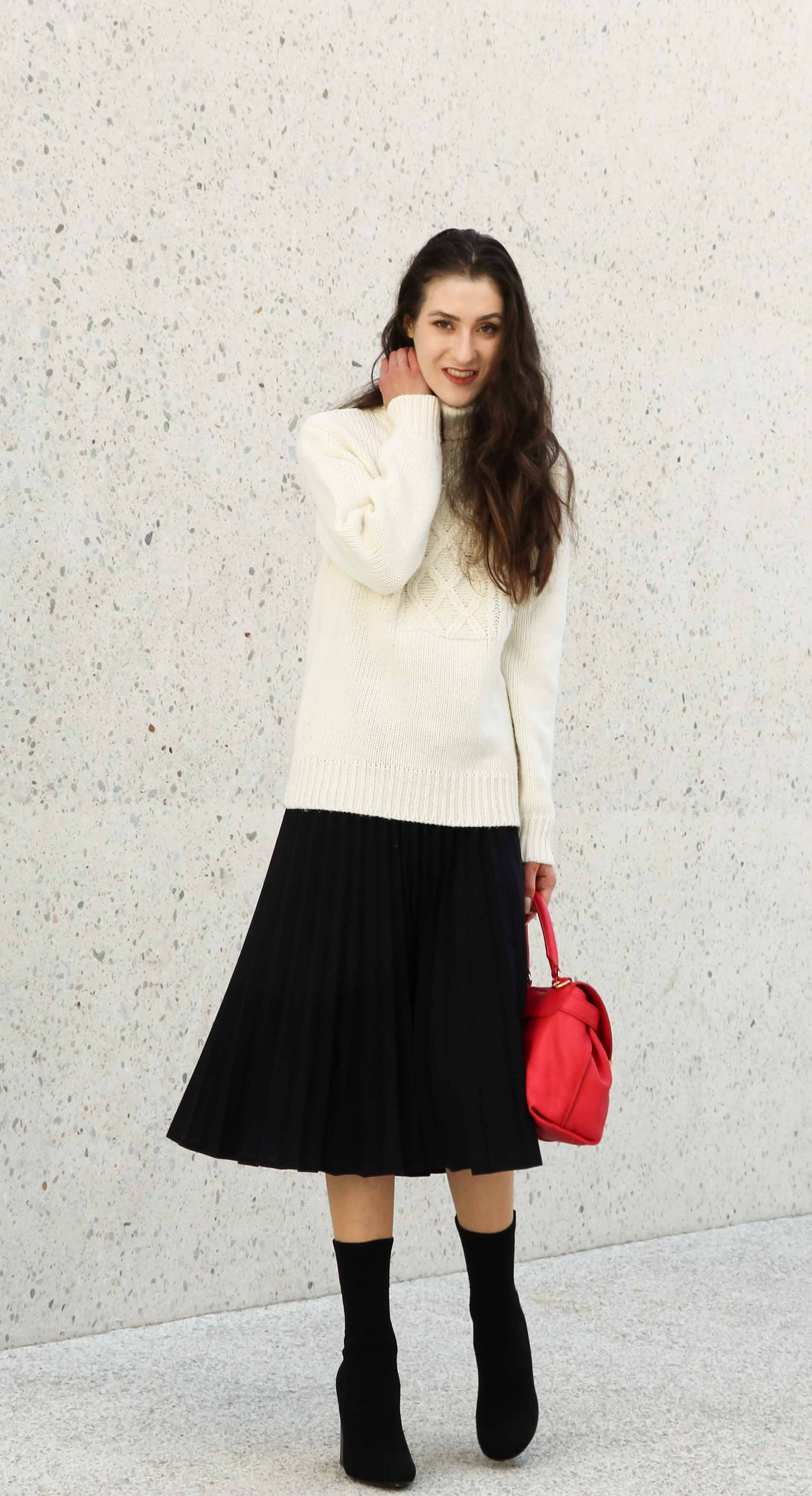 Fashion Blogger Veronika Lipar of Brunette from Wall Street dressed in white oversized turtleneck sweater, black midi skirt with pleats, pink top handle bag from See by Chloe and black sock boots from Elena Iachi this winter