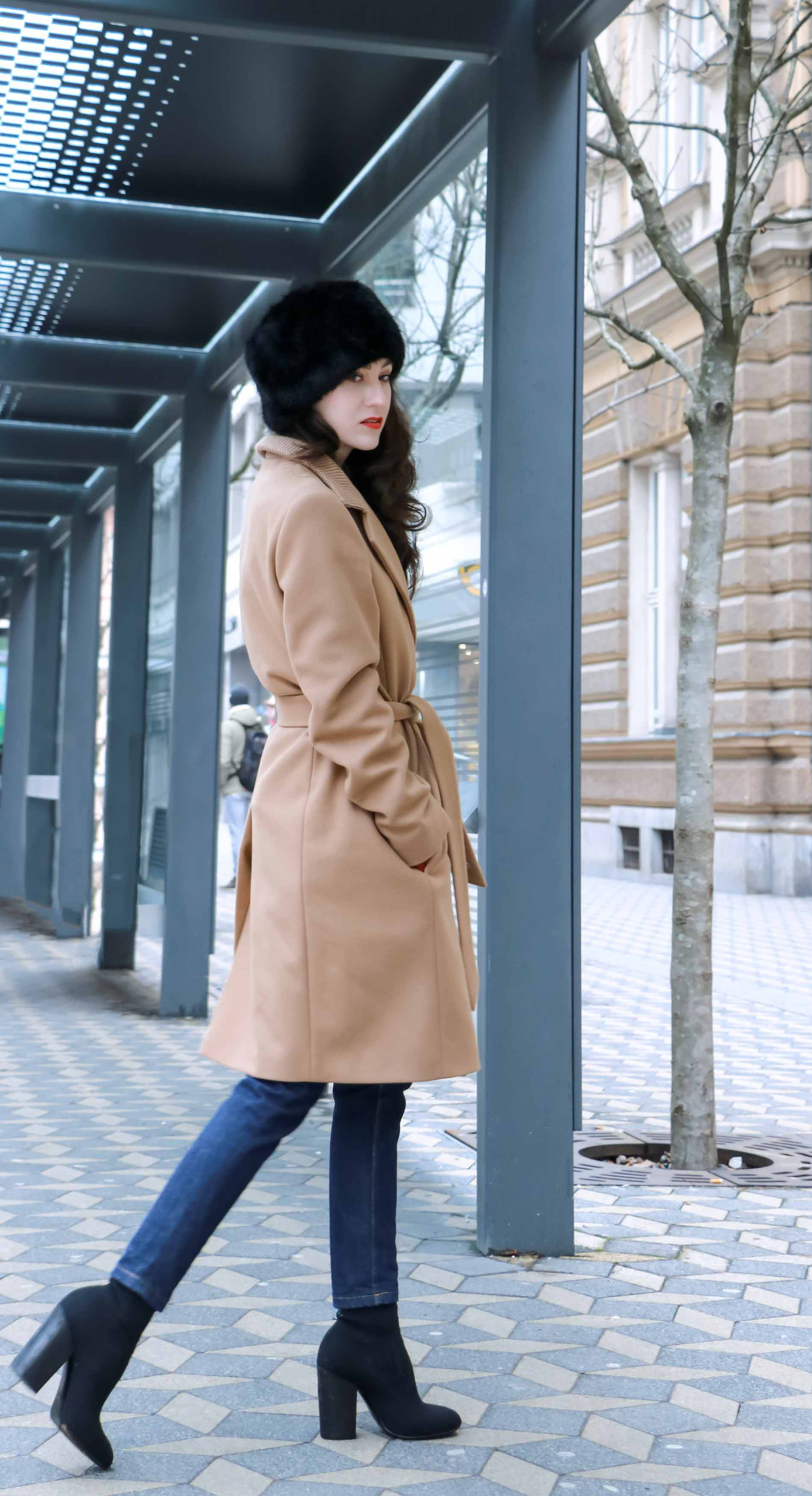 Veronika Lipar of Brunette from Wall Street wearing wrap Escada camel coat, A.P.C. dark tapered denim jeans, black sock boots from Elena Iachi, black fur hat and small black top handle bag while passing by the bus station
