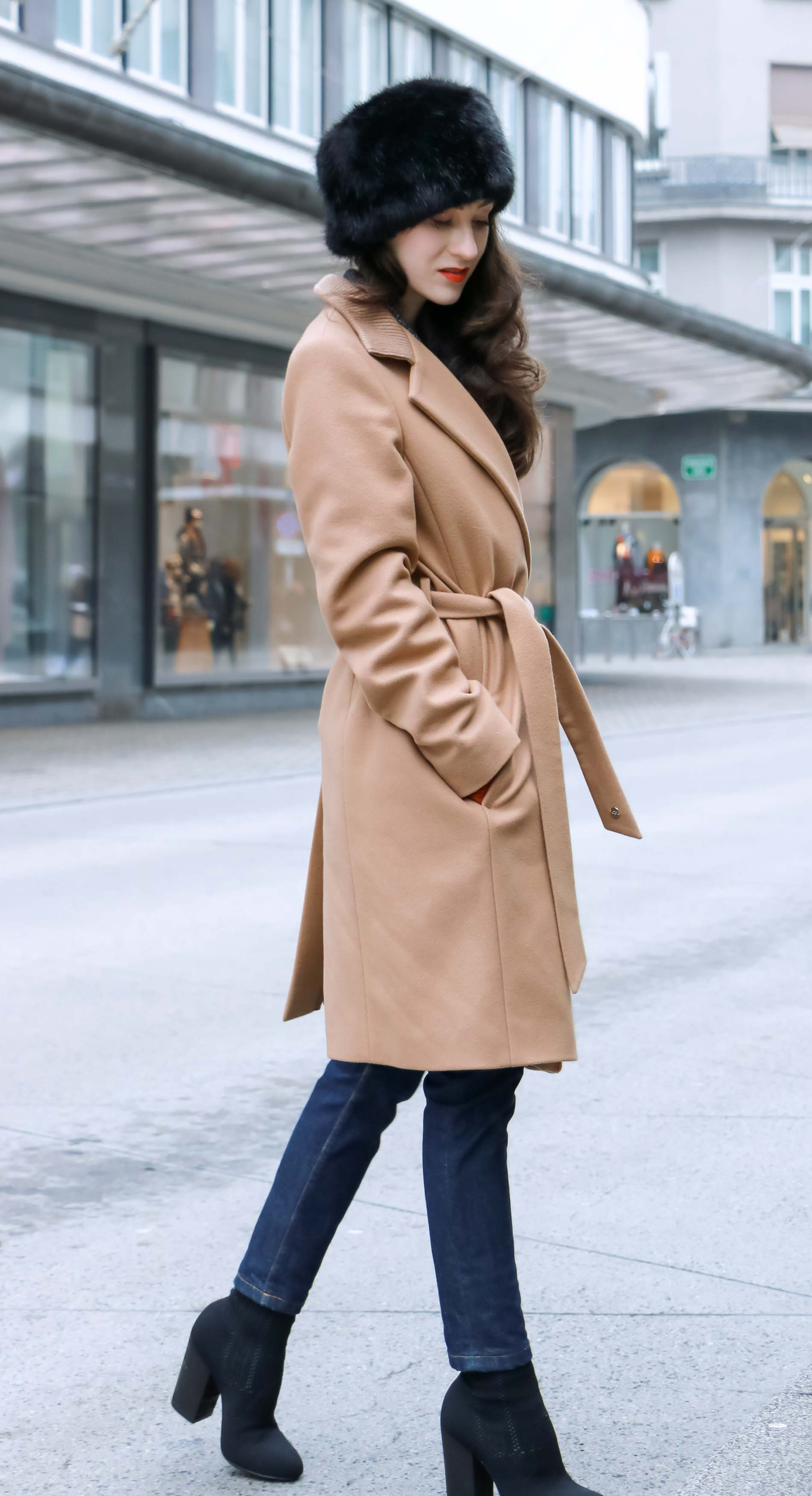 Veronika Lipar of Brunette from Wall Street dressed in wrap Escada camel coat, A.P.C. dark tapered denim jeans, black sock boots from Elena Iachi, black fur hat and small black top handle bag while crossing street in Ljubljana
