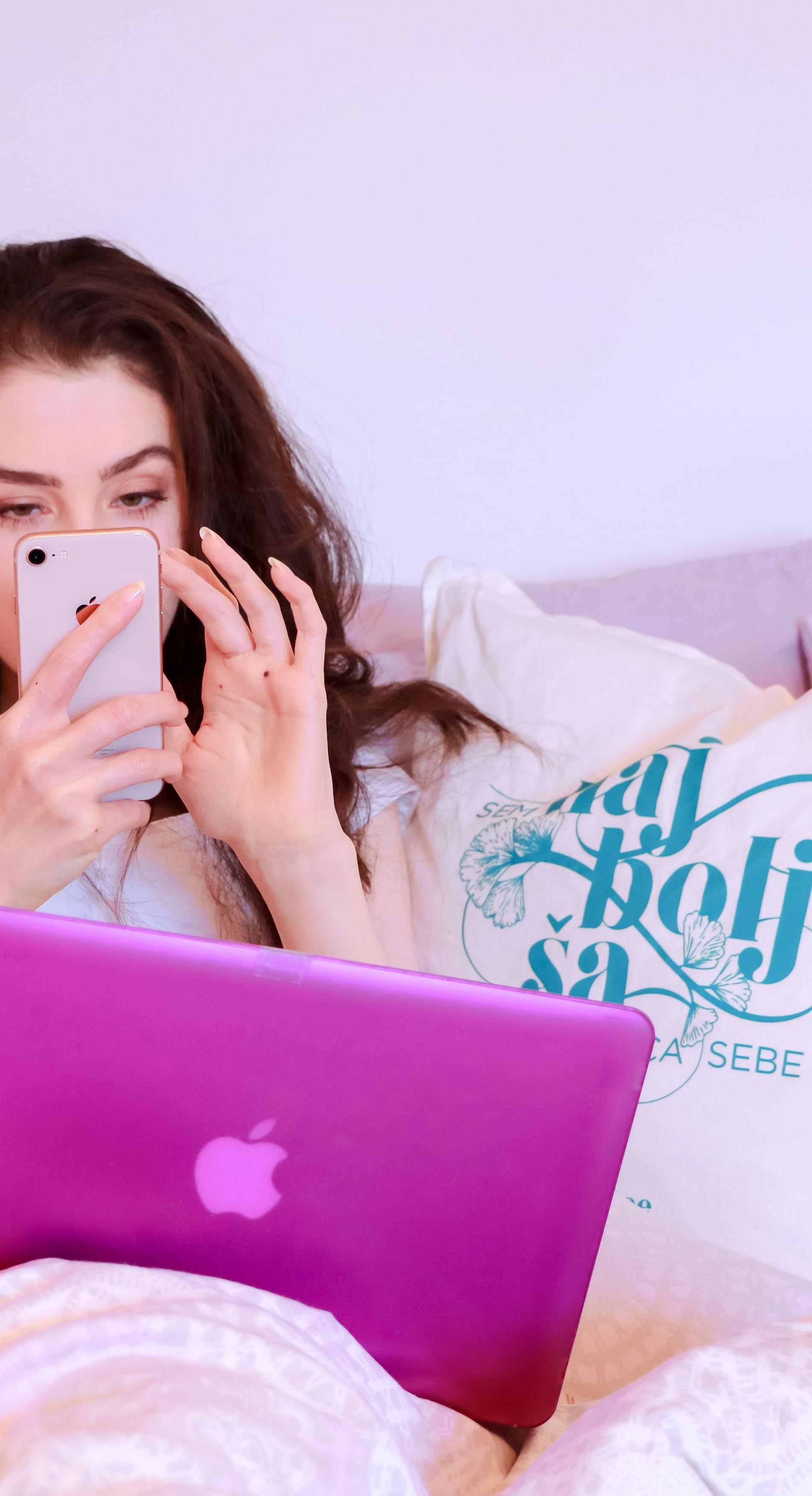 Fashion Blogger Veronika Lipar of Brunette from Wall Street checking her iPhone while Netflix and chilling on her pink MacBook while sitting in the pink bed surrounded by pink pillows