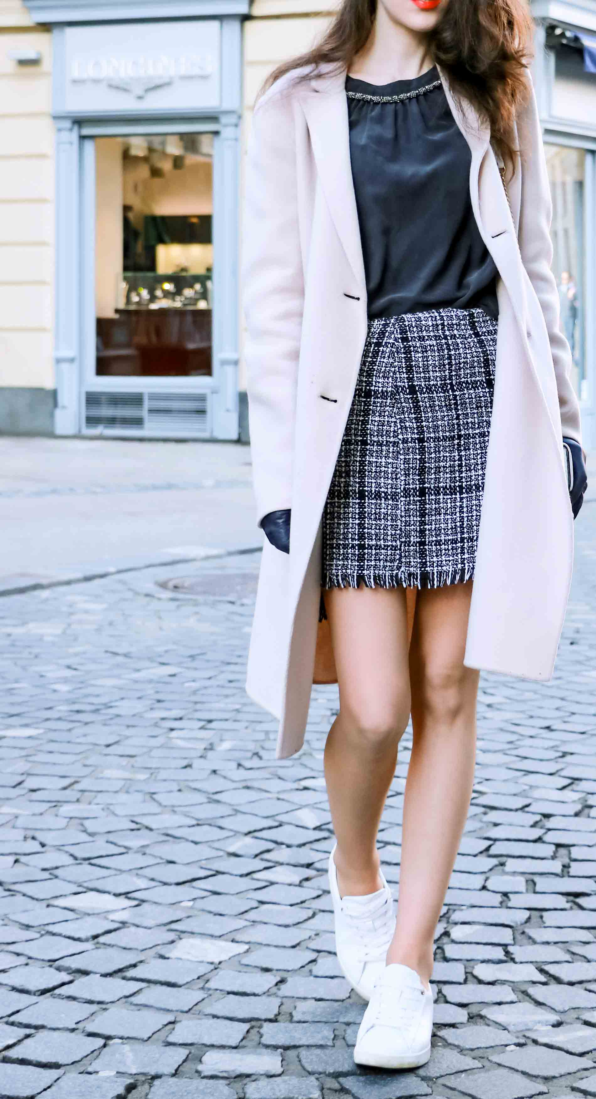 Fashion Blogger Veronika Lipar of Brunette from Wall Street dressed in white sneakers from Diesel, black and white plaid tweed mini skirt from Storets, black silk blouse from Juicy Couture, off-white double breasted wool coat from MaxMara, faux fur headband, white shoulder bag with gold chain strap, blue leather gloves walking down the street in Ljubljana