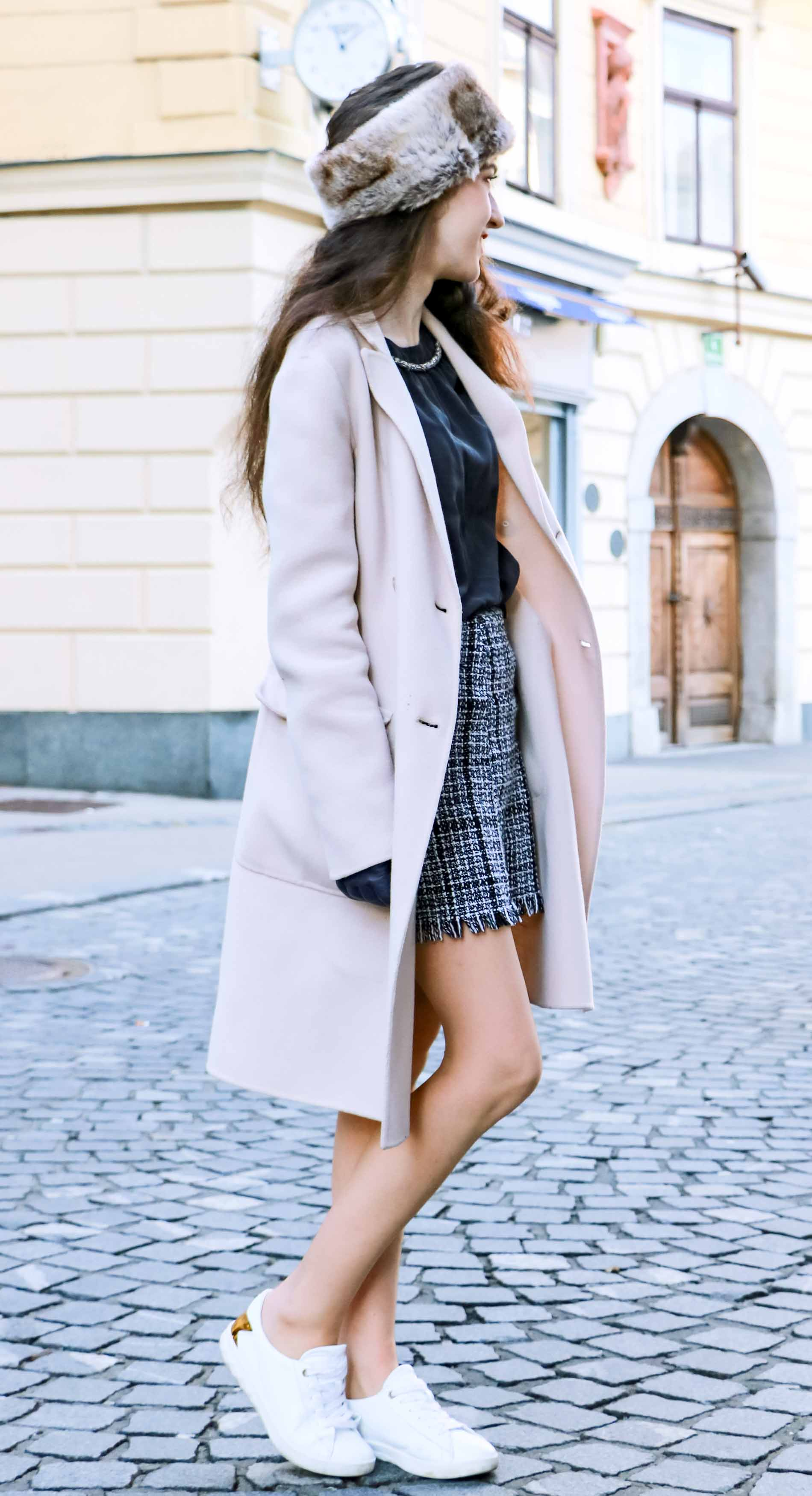 Fashion Blogger Veronika Lipar of Brunette from Wall Street wearing black and white plaid tweed mini skirt from Storets, black silk blouse from Juicy Couture, off-white double breasted wool coat from MaxMara, faux fur headband, chain strap shoulder white bag, blue leather gloves on the street in Ljubljana