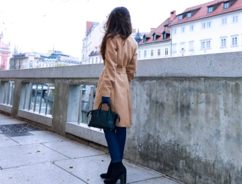 Fashion Blogger Veronika Lipar of Brunette from Wall Street dressed in camel wrap coat from Escada, tapered dark denim jeans from A.P.C., white tailored fringed shirt, small black top handle bag, blue leather gloves and red lipstick, business casual outfit for work, on the street in Ljubljana