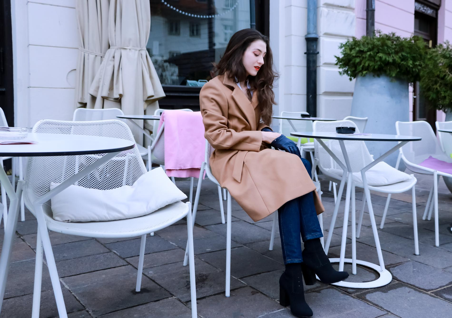 Fashion Blogger Veronika Lipar of Brunette from Wall Street dressed in camel wrap coat from Escada, tapered dark denim jeans from A.P.C., small black top handle bag, blue leather gloves and red lipstick, business casual outfit for work, having coffee time in Ljubljana