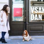 Fashion Blogger Veronika Lipar of Brunette from Wall Street dressed in chic casual winter outfit on the street in Ljubljana in on the warm the morning looking at dog