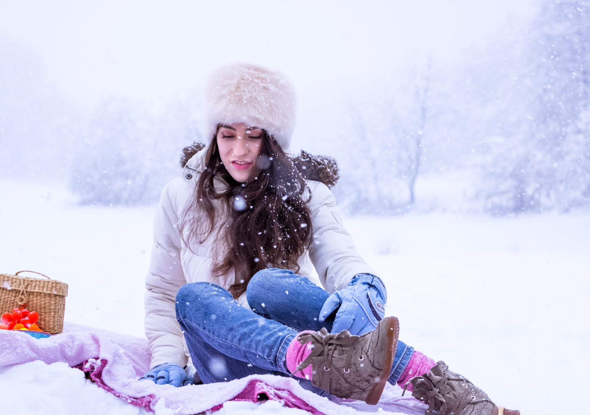 Fashion Blogger Veronika Lipar of Brunette from Wall Street wearing white down puffer jacket, blue jeans, blue snow gloves, white faux fur hat, pink wool socks and Isabel Marant Bobby sneakers, sitting on a pink picnic blanket in the snow