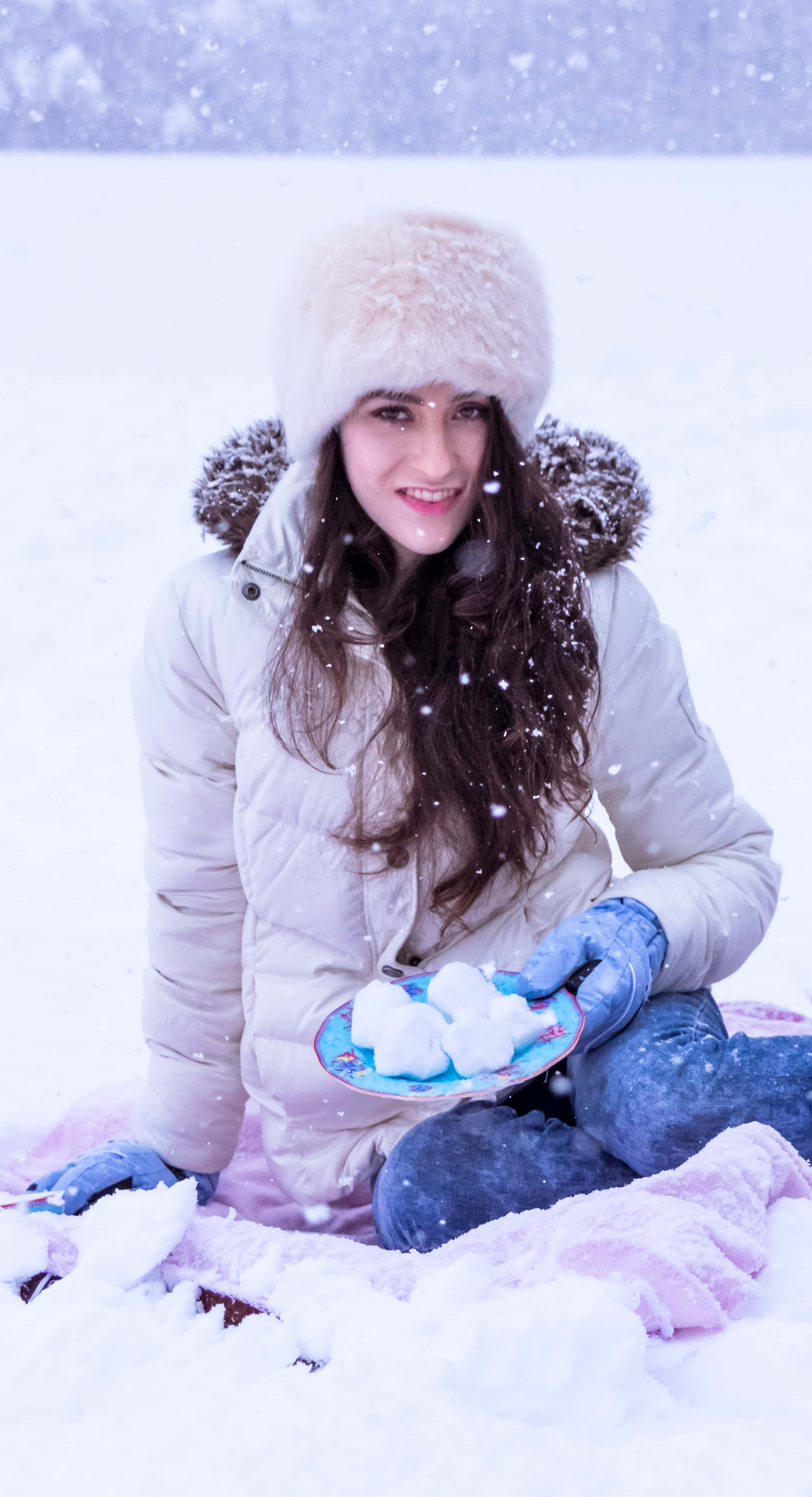 Fashion Blogger Veronika Lipar of Brunette from Wall Street dressed in white down puffer jacket, blue jeans, blue snow gloves, white faux fur hat, pink wool socks and Isabel Marant Bobby sneakers on her winter picnic