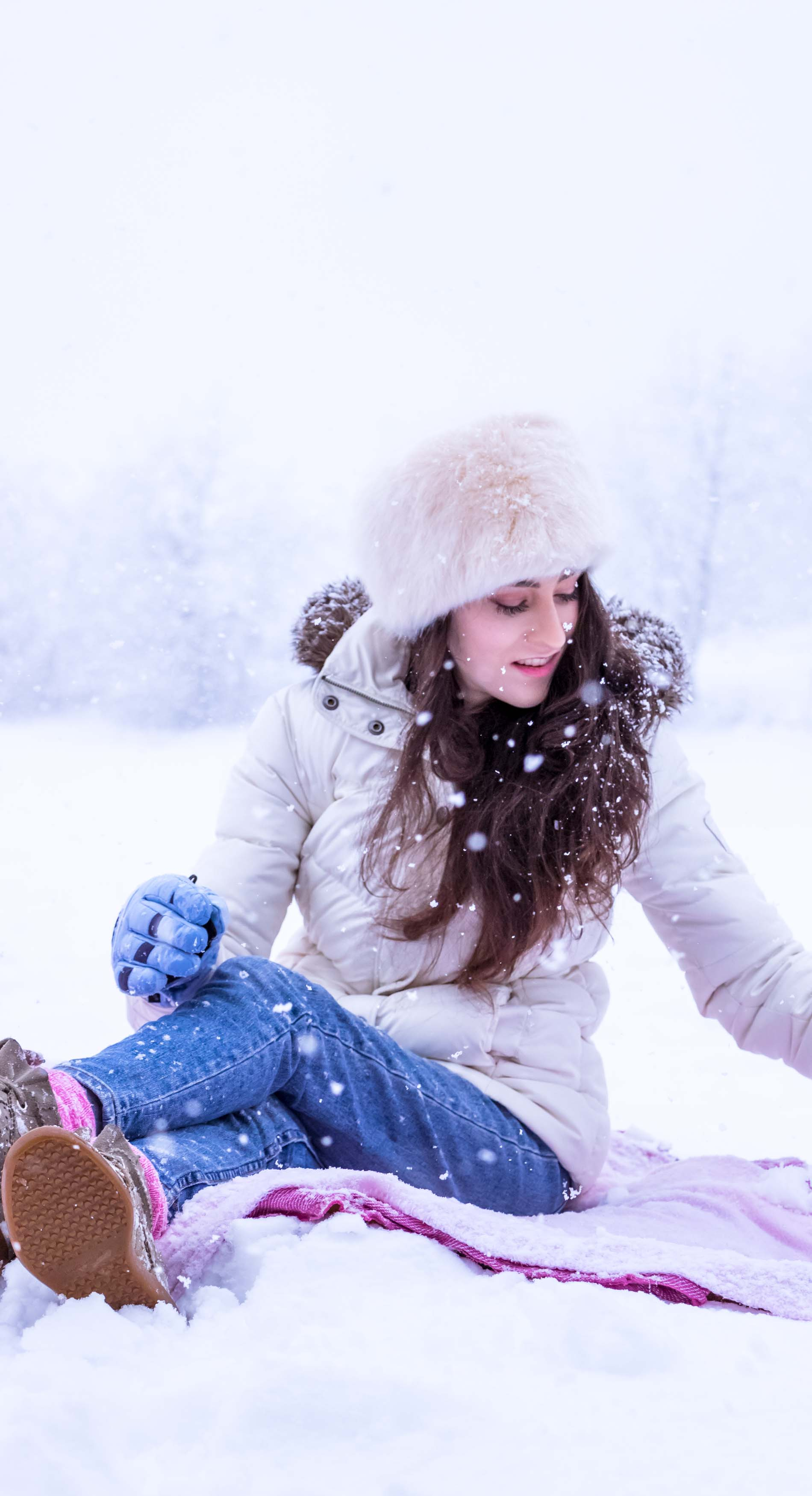 Fashion Blogger Veronika Lipar of Brunette from Wall Street wearing white down puffer jacket, blue jeans, blue snow gloves, white faux fur hat, pink wool socks and Isabel Marant Bobby sneakers, playing in the snow