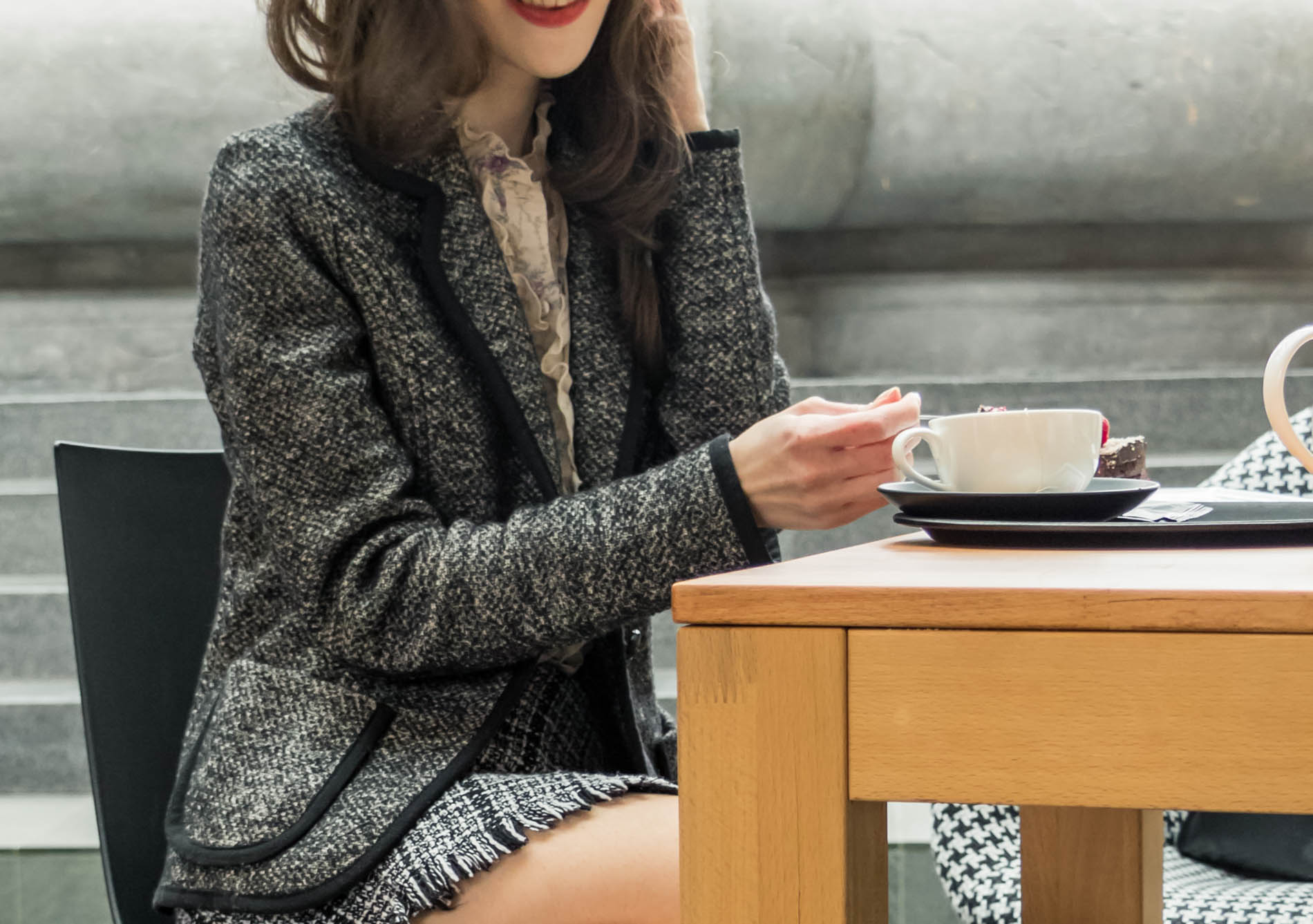 Fashion Blogger Veronika Lipar of Brunette from Wall Street dressed in tweed plaid mini skirt from Storets, black and white Marella tweed jacket, while drinking coffee