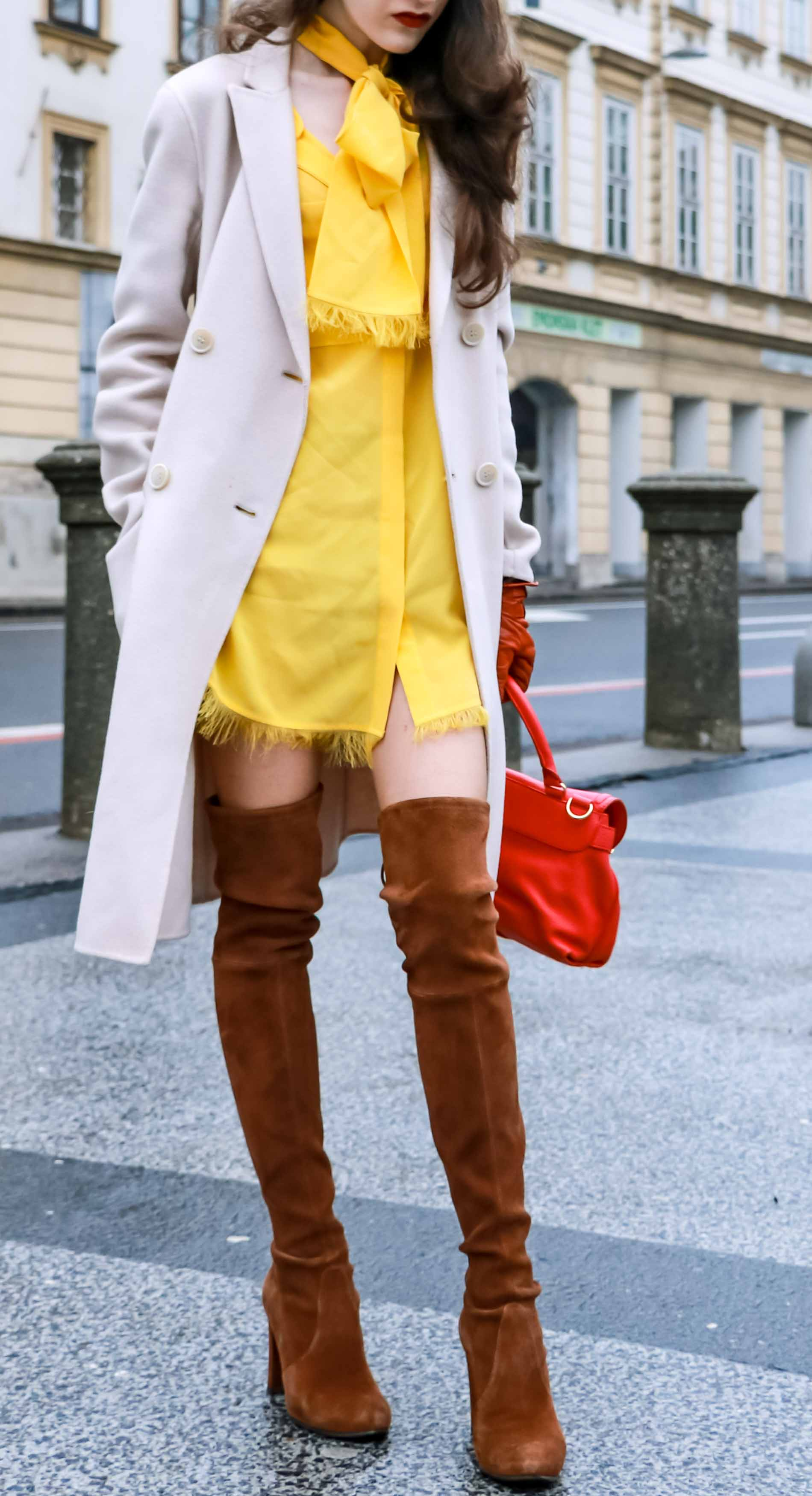 Fashion Blogger Veronika Lipar of Brunette from Wall Street dressed in the IT dress of spring summer 2018, the yellow dress from Escada, off-white, pastel double-breasted coat from Weekend Maxmara, pink top handle bag from See by Chloé, brown Stuart Weitzman over the knee boots, and faux fur headband at the end of winter