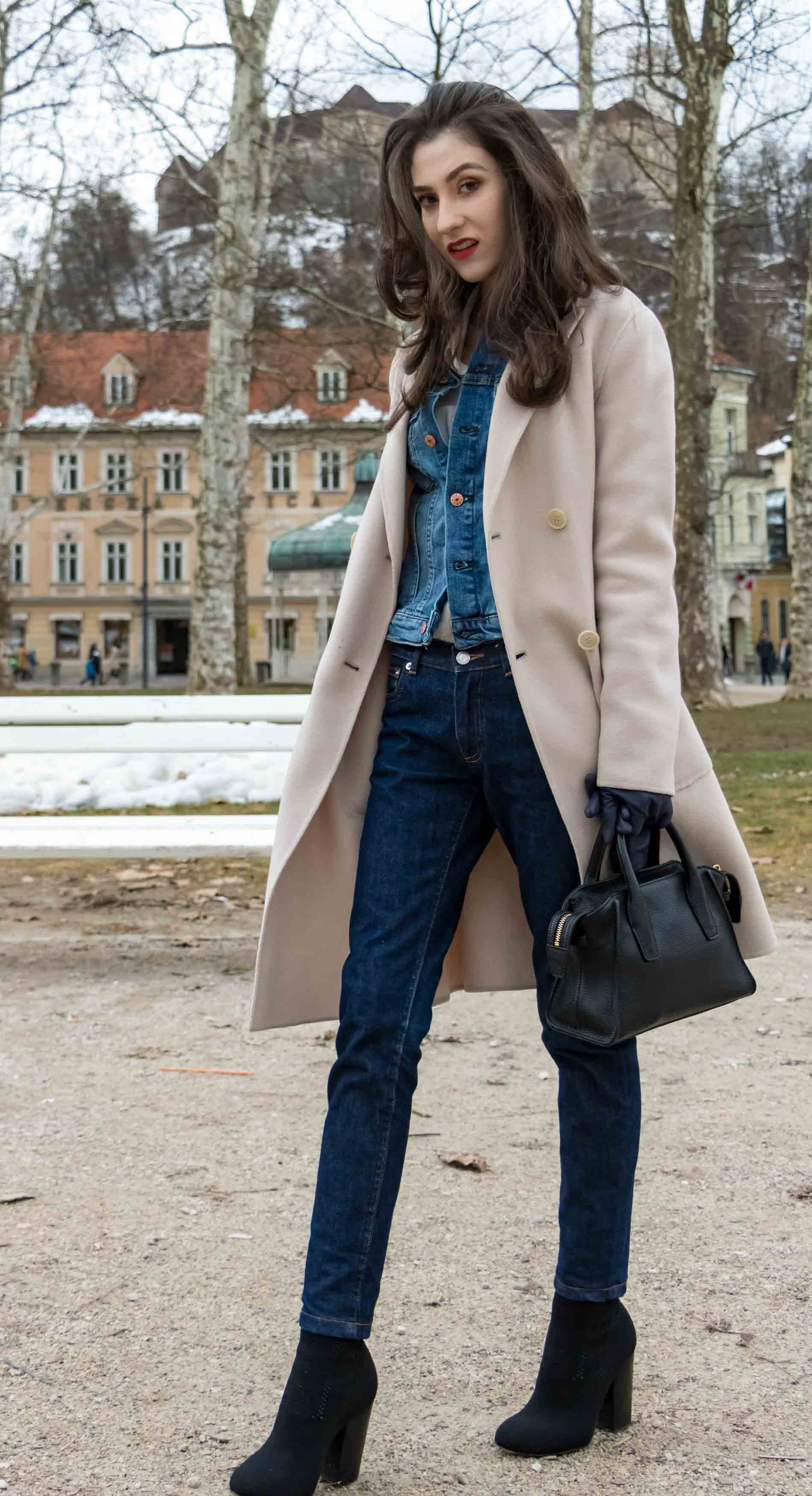Fashion Blogger Veronika Lipar of Brunette from Wall Street wearing chic casual denim on denim trend, blue cropped denim jacket from H&M, with tapered straight-leg dark blue denim jeans from A.P.C., pastel pink, off-white double breasted Weekend Maxmara coat, black top handle bag, blue leather gloves and black sock ankle boots from Elena Iachi on the last days of winter