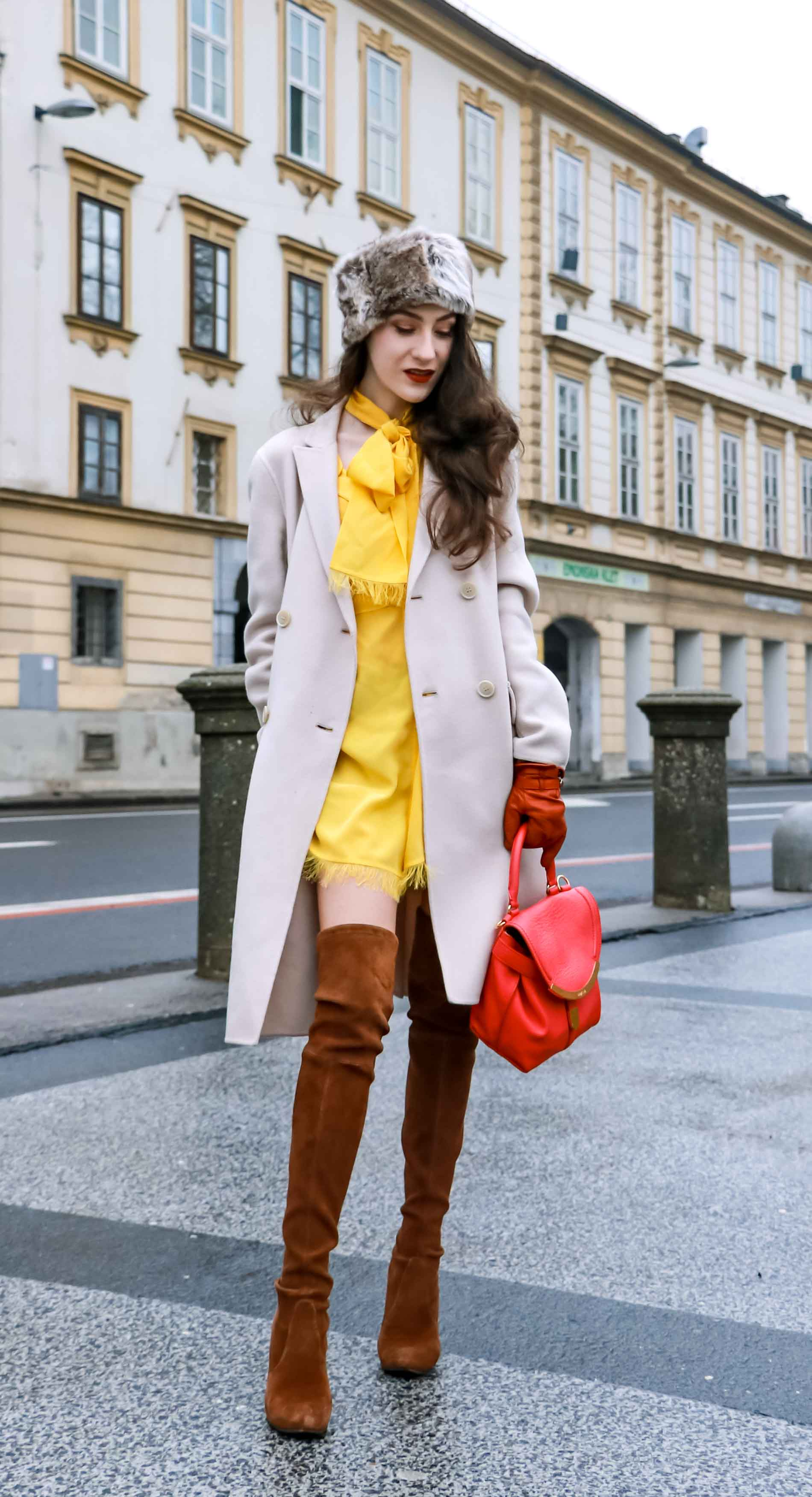 Fashion Blogger Veronika Lipar of Brunette from Wall Street wearing the IT dress of spring summer 2018, the yellow dress from Escada, off-white, pastel double-breasted coat from Weekend Maxmara, pink top handle bag from See by Chloé, brown Stuart Weitzman over the knee boots, and faux fur headband in winter