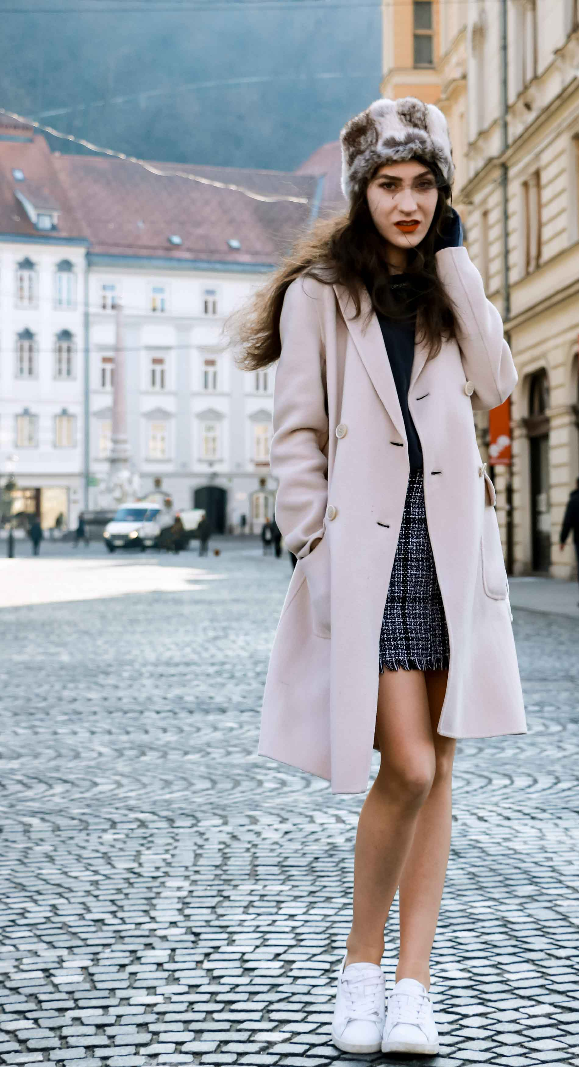 Fashion Blogger Veronika Lipar of Brunette from Wall Street wearing white sneakers from Diesel, black and white plaid tweed mini skirt from Storets, black silk blouse from Juicy Couture, off-white double breasted wool coat from MaxMara, faux fur headband, chain strap shoulder white bag, blue leather gloves on the street in Ljubljana
