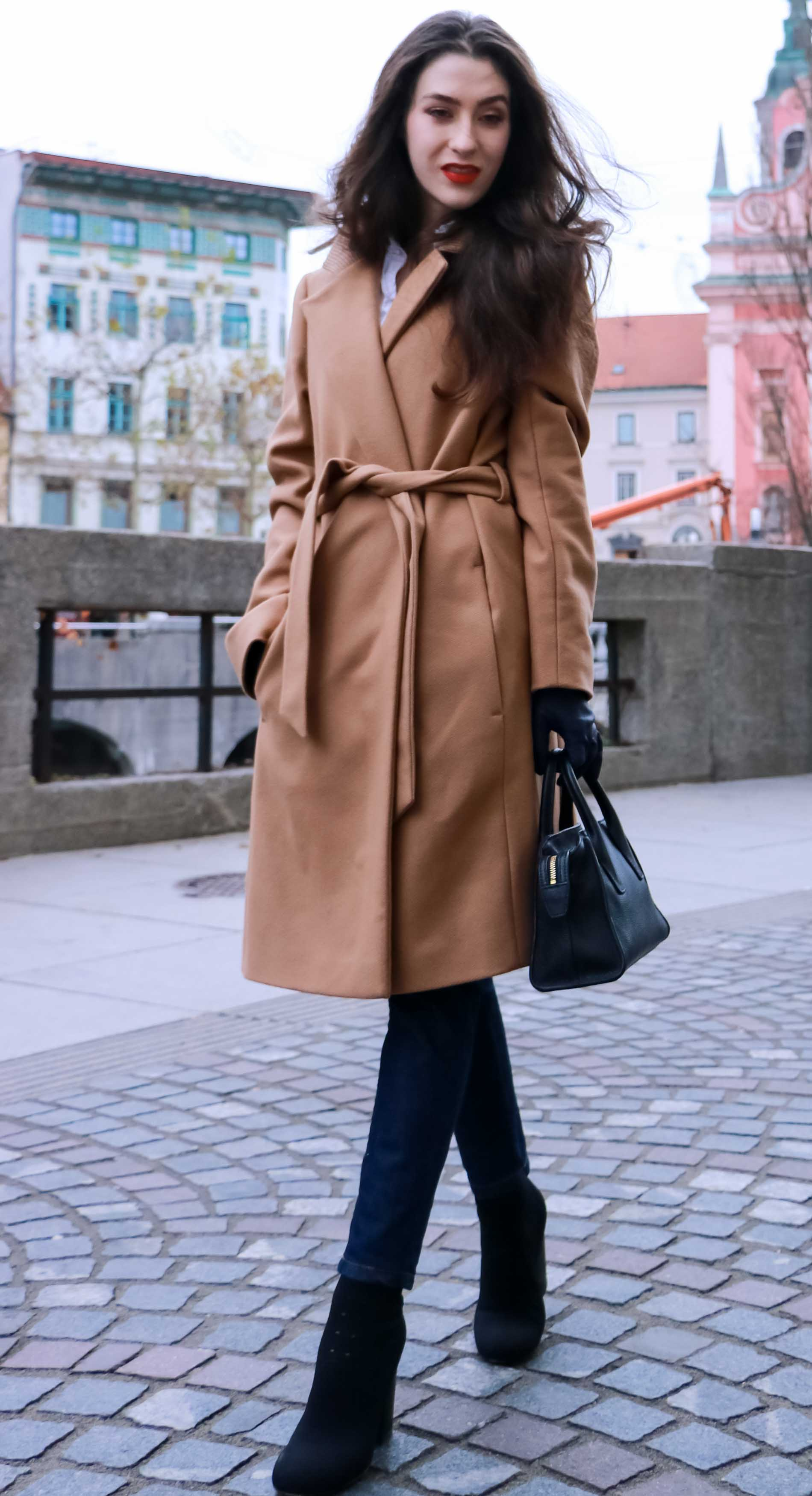 Fashion Blogger Veronika Lipar of Brunette from Wall Street wearing camel wrap coat from Escada, tapered dark denim jeans from A.P.C., small black top handle bag, blue leather gloves and red lipstick, business casual outfit for work, while walking down the street in Ljubljana