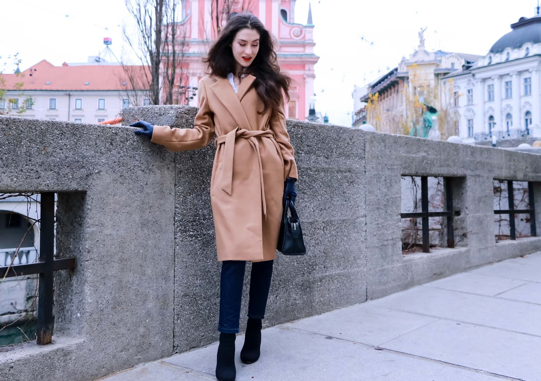 Fashion Blogger Veronika Lipar of Brunette from Wall Street wearing camel wrap coat from Escada, tapered dark denim jeans from A.P.C., small black top handle bag, blue leather gloves and red lipstick, business casual outfit for work, while standing on the street in Ljubljana