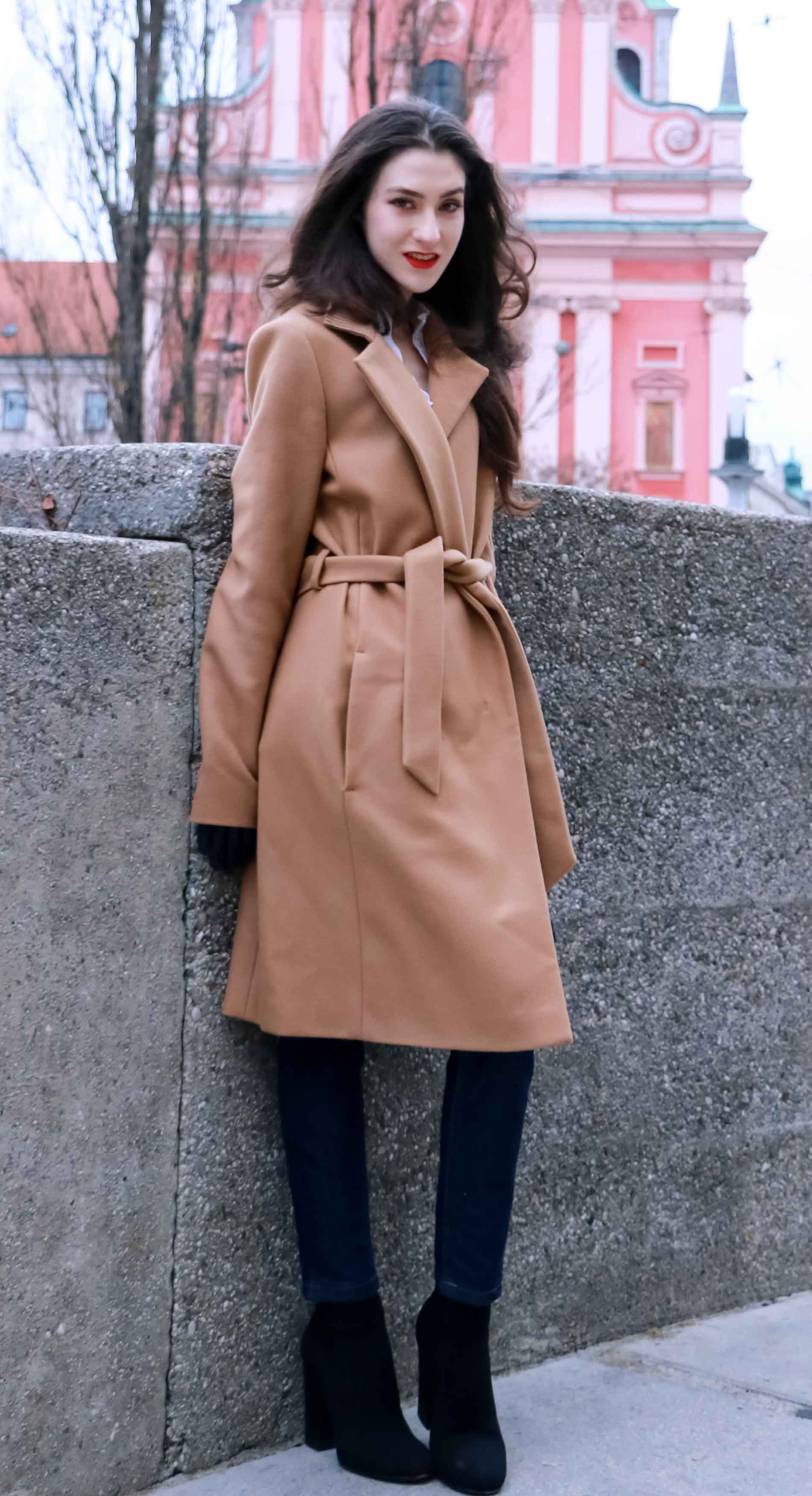 Fashion Blogger Veronika Lipar of Brunette from Wall Street dressed in camel wrap coat from Escada, tapered dark denim jeans from A.P.C., small black top handle bag, blue leather gloves and red lipstick, business casual outfit for work, while standing on the street in Ljubljana