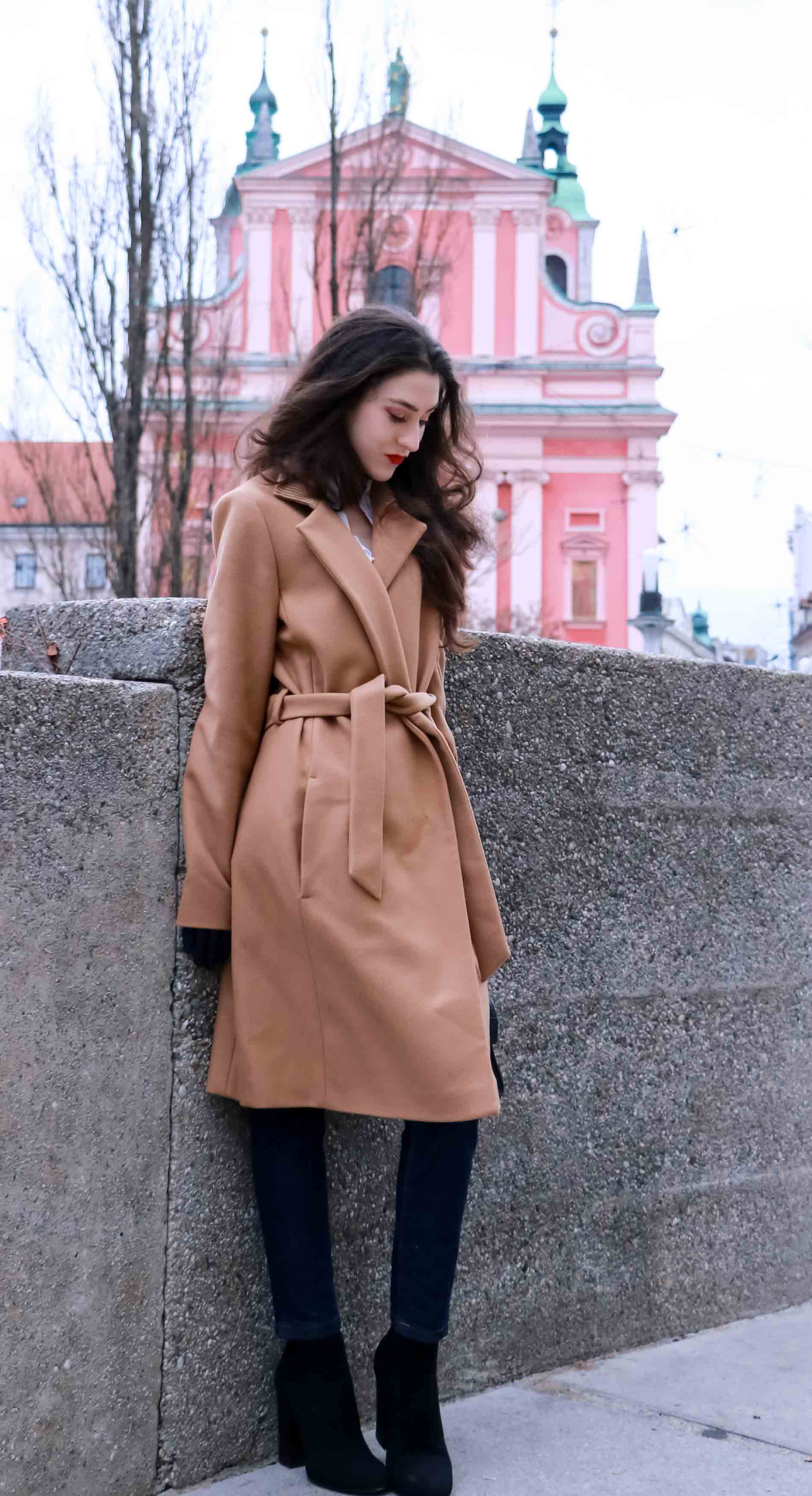 Fashion Blogger Veronika Lipar of Brunette from Wall Street dressed in camel wrap coat from Escada, tapered dark denim jeans from A.P.C., small black top handle bag, blue leather gloves and red lipstick, business casual outfit for work