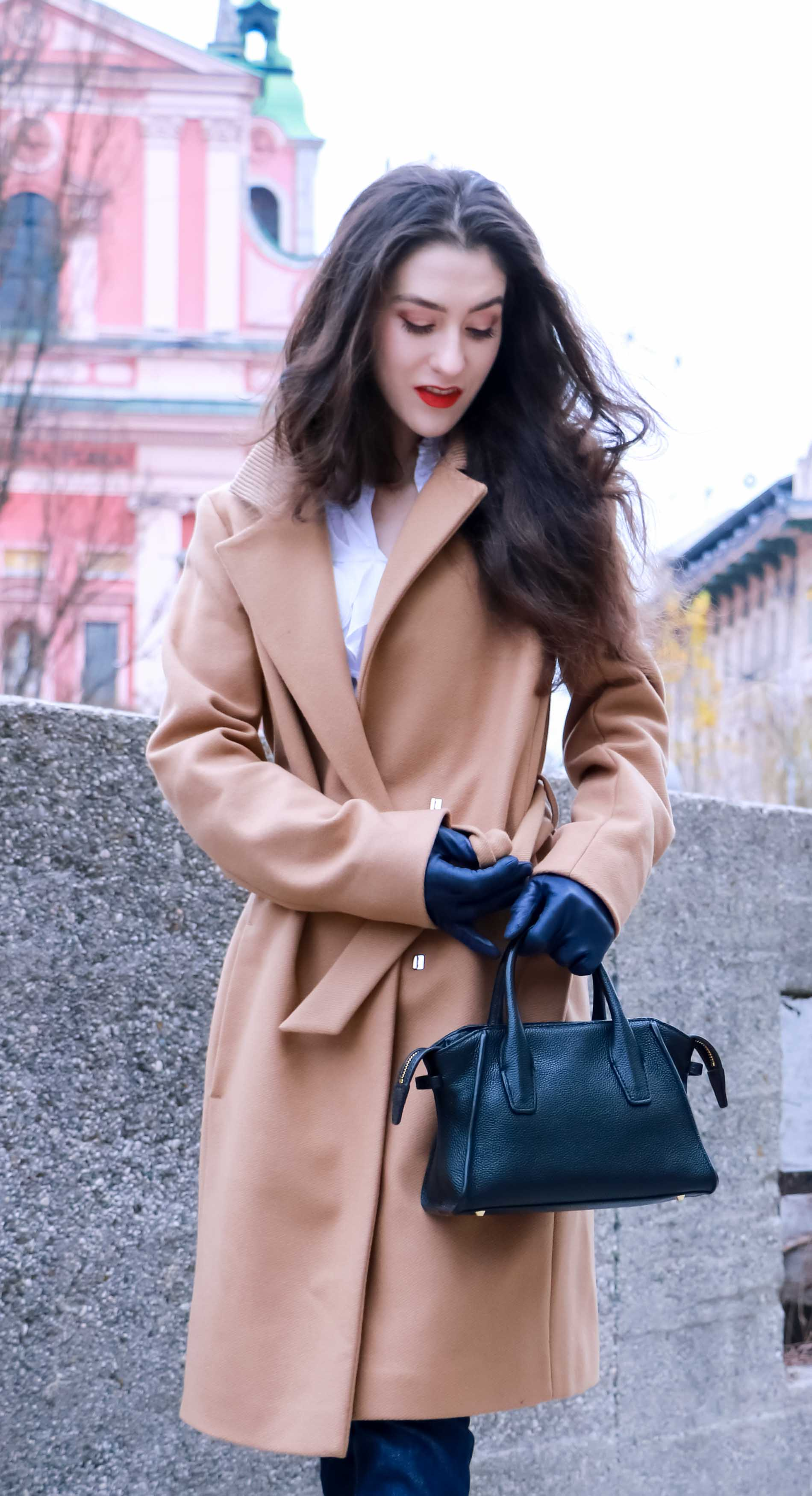 Fashion Blogger Veronika Lipar of Brunette from Wall Street dressed in camel wrap coat from Escada, tapered dark denim jeans from A.P.C., white tailored fringed shirt, small black top handle bag, blue leather gloves and red lipstick, business casual outfit for work, untieying her coat
