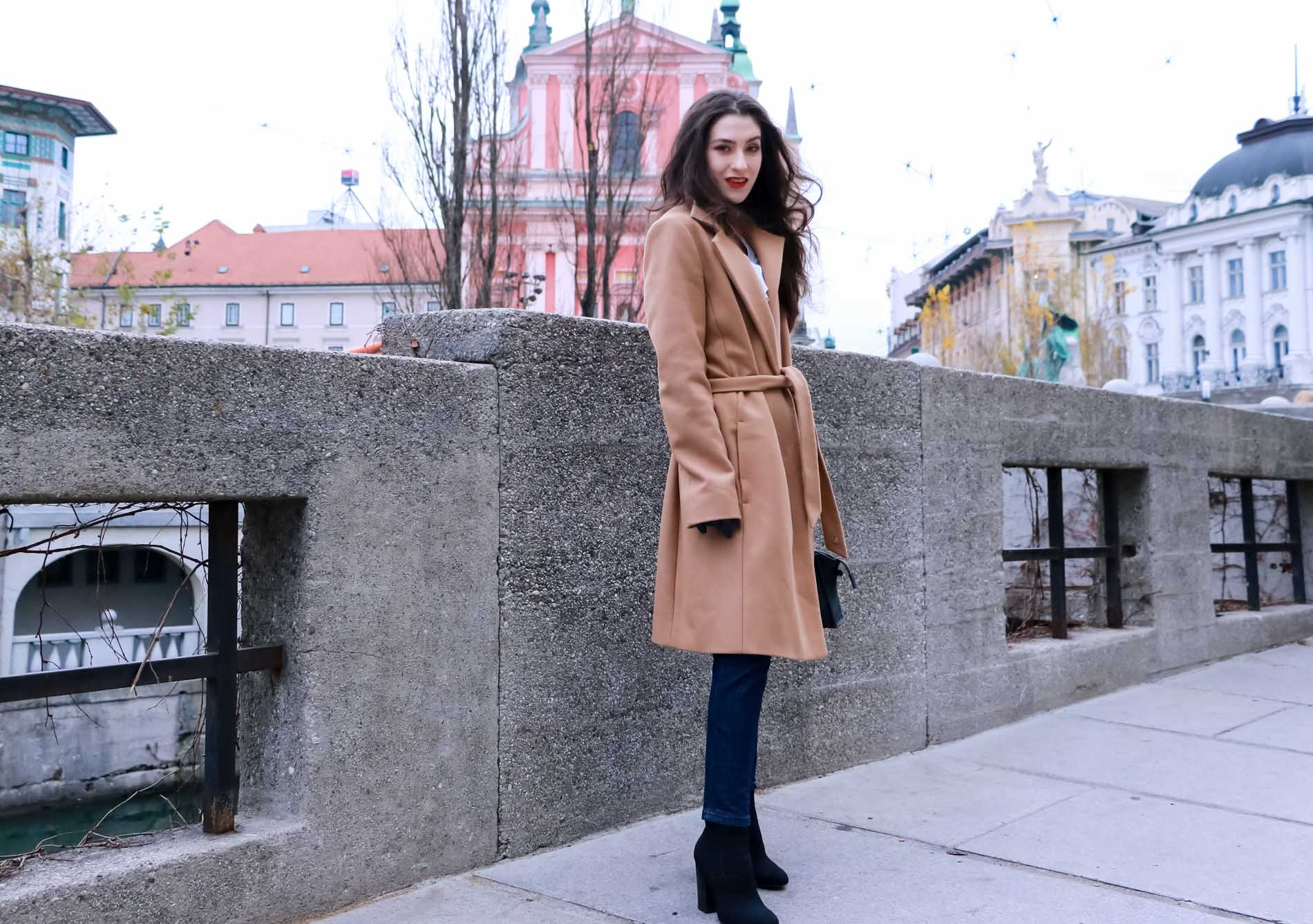 Fashion Blogger Veronika Lipar of Brunette from Wall Street wearing camel wrap coat from Escada, tapered dark denim jeans from A.P.C., small black top handle bag, blue leather gloves and red lipstick, business casual outfit for work, on the street in Ljubljana